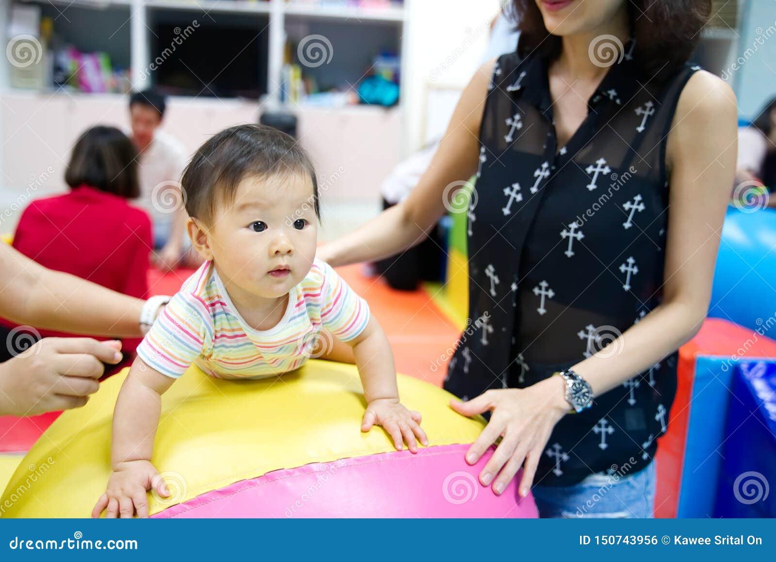 Ung liten asiat att behandla som ett barn för att tycka om spela på färgrik boll i ungelekplats