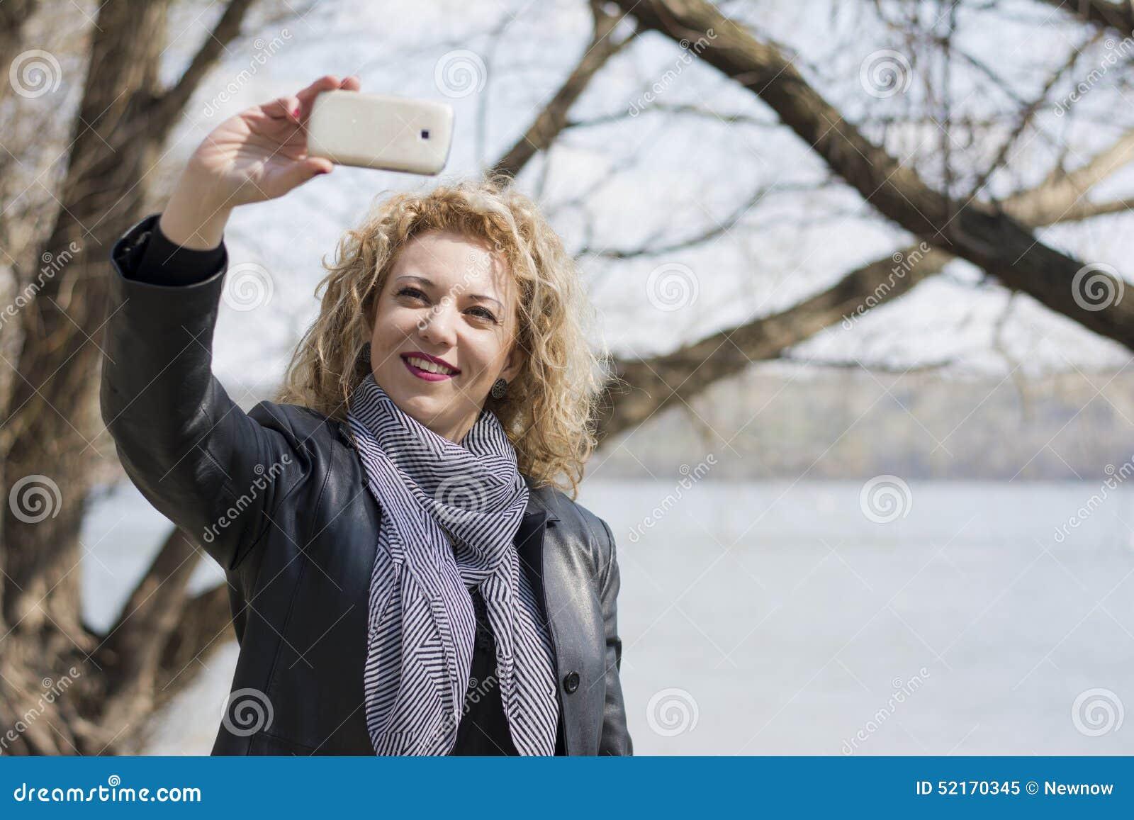 Ung lockig blond kvinna som tar bilden av henne