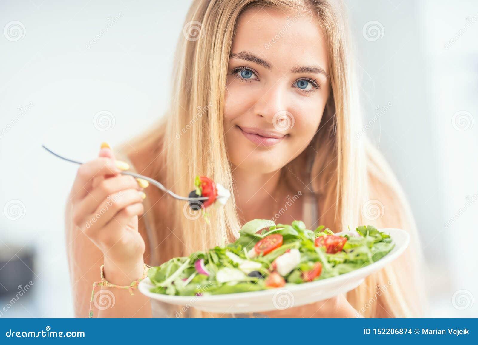 Ung lycklig blond flicka som äter sund sallad från oliv lök och olivolja för arugulaspenattomater