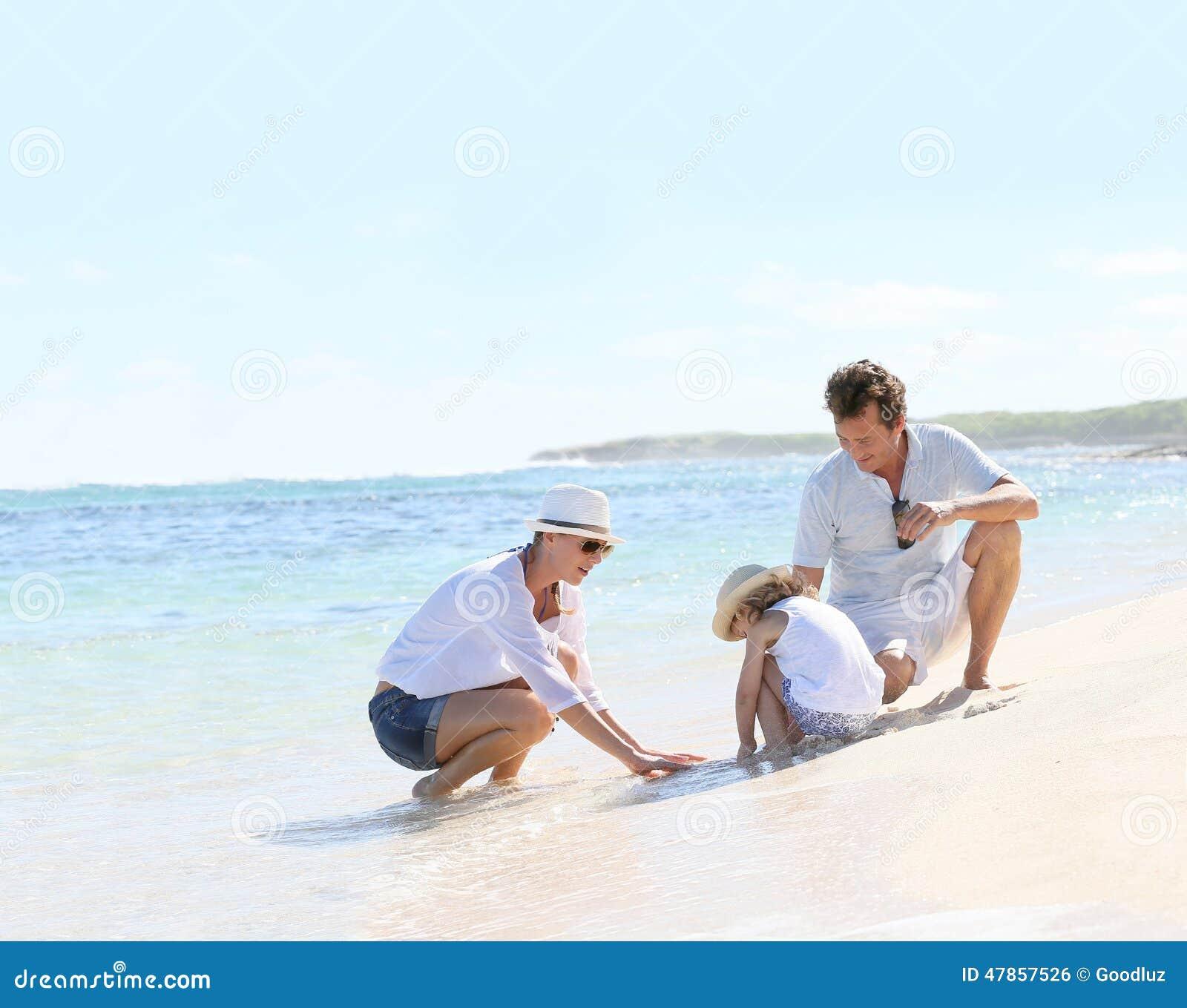 Ung lycklig familj som spenderar tid på stranden
