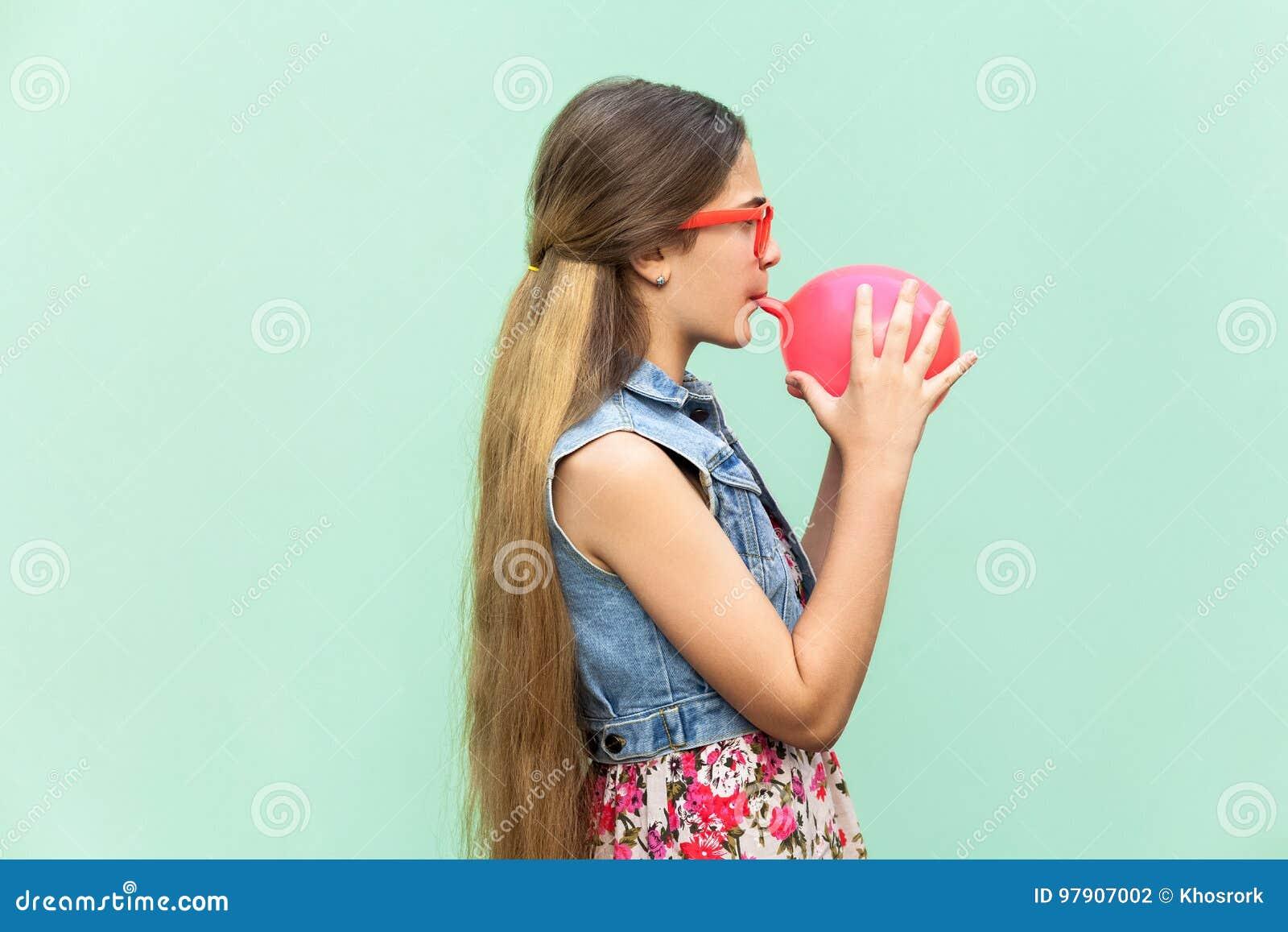 Ung lycklig flicka som blåser ballonger för födelsedagparti som ser roliga på kameran på ett ljus - grön bakgrund