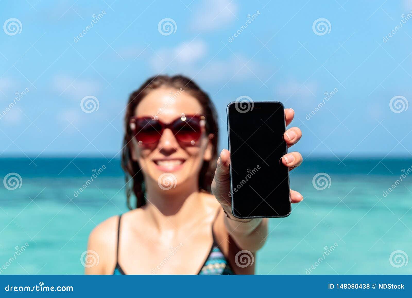 Ung lycklig kvinna som visar en vertikal telefonskärm Klart bl?tt vatten som bakgrund