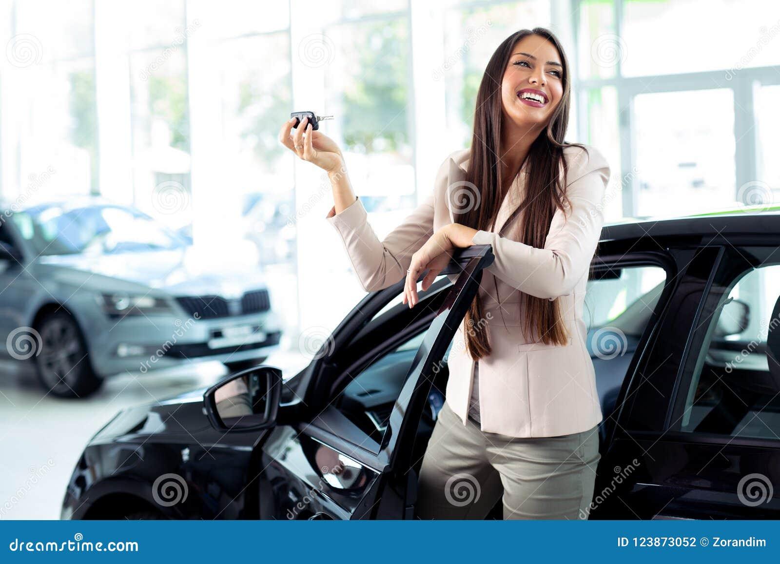 Ung lycklig kvinna som visar tangenten av den nya bilen