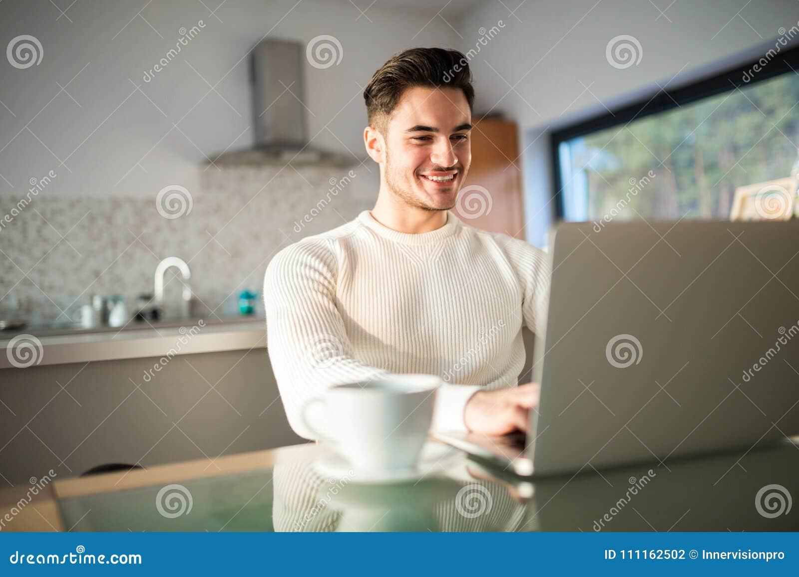 Ung lycklig man som hemma arbetar på bärbara datorn