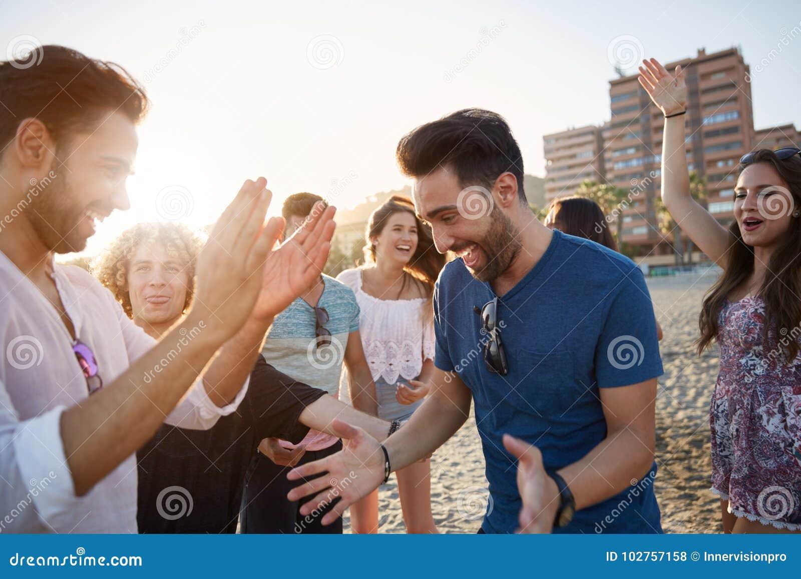 Ung lycklig mandans på stranden med vänner