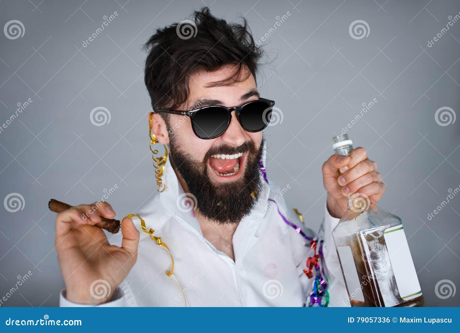 Ung lycklig skäggig man som har en drink på grå bakgrund
