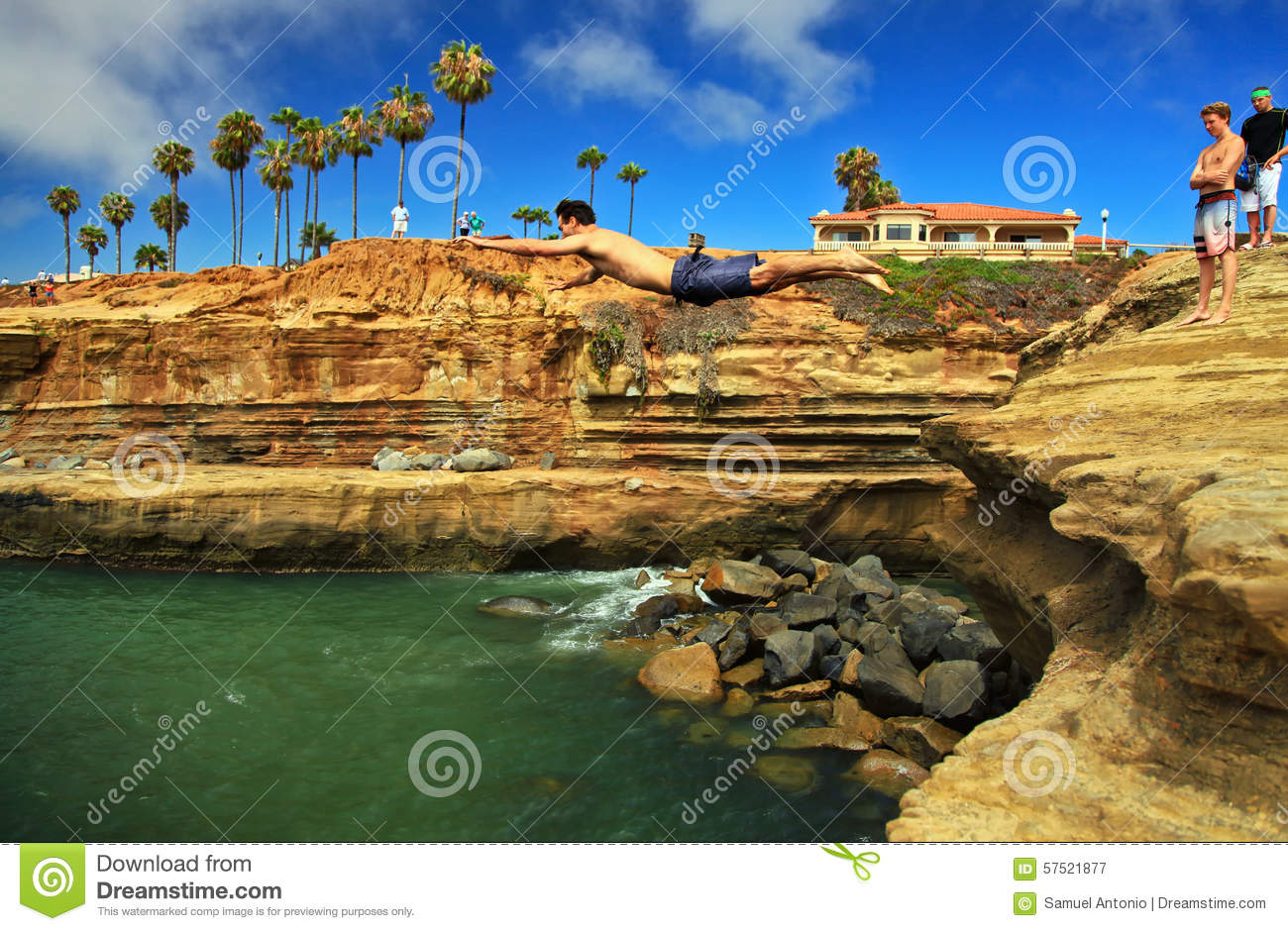 Ung man Cliff Diving in i vatten, solnedgångklippor, Point Loma, San Diego, Kalifornien