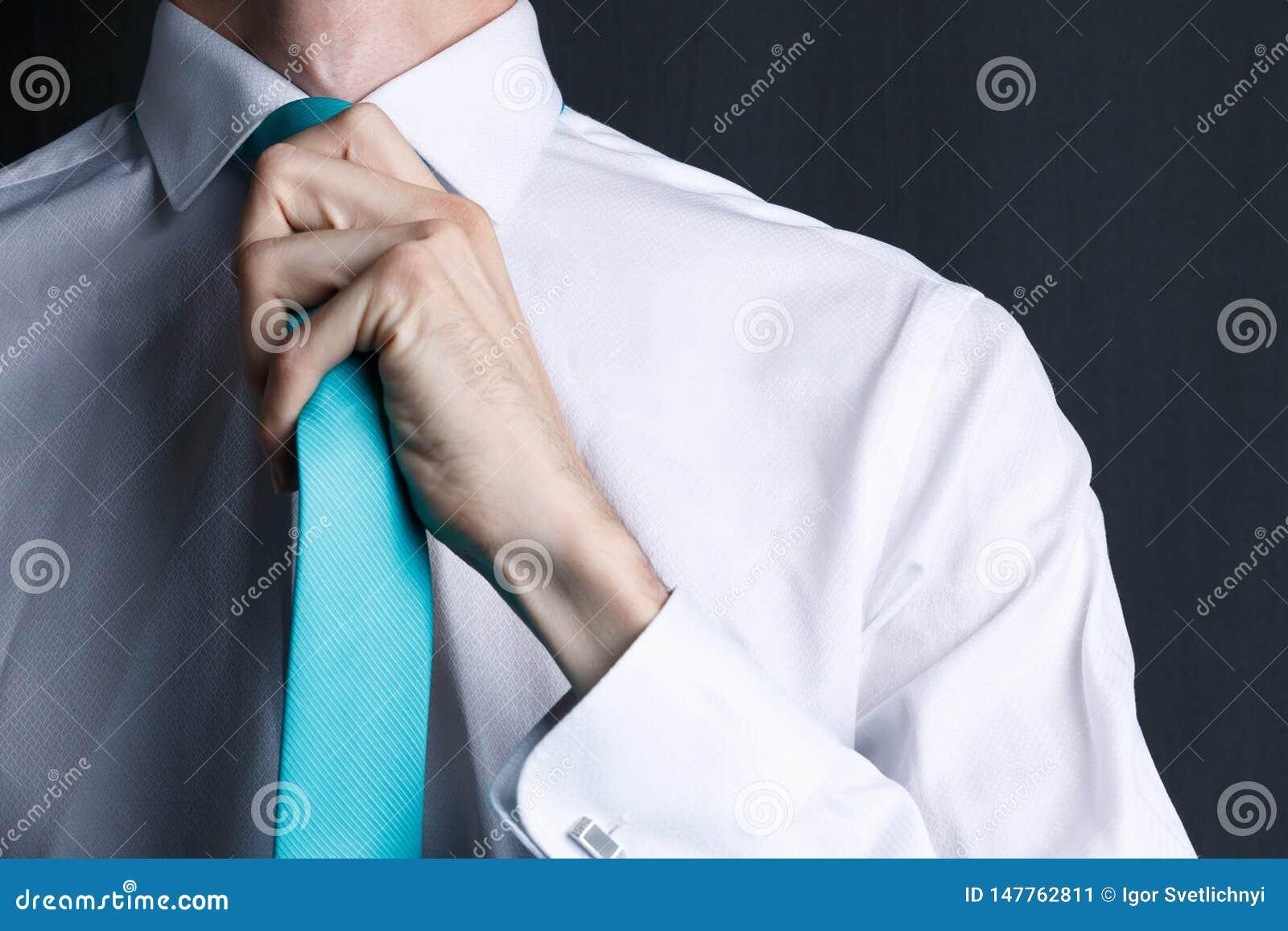 Ung man f?r n?rbild i en vit skjorta med ett band Mannen r?tar ut hans band, hans orakade framsida Aff?rsman i en vit skjorta