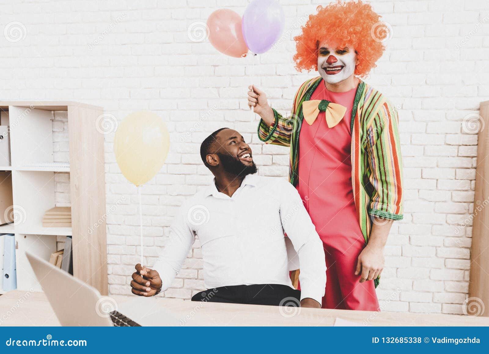 Ung man i clownen Costume med Baloons i regeringsställning