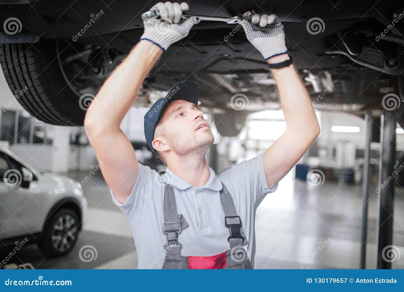 Ung man i process av att arbeta under bilen Han ser upp till höger och rymmer den stora skiftnyckeln med båda händer Han är
