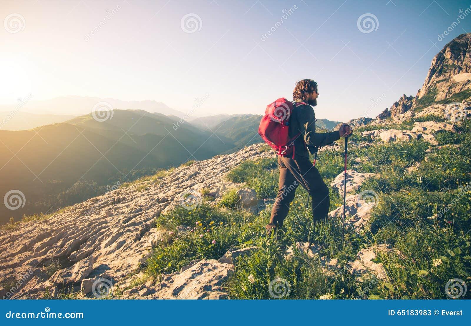 Ung man med att klättra i berg för ryggsäck som är utomhus-