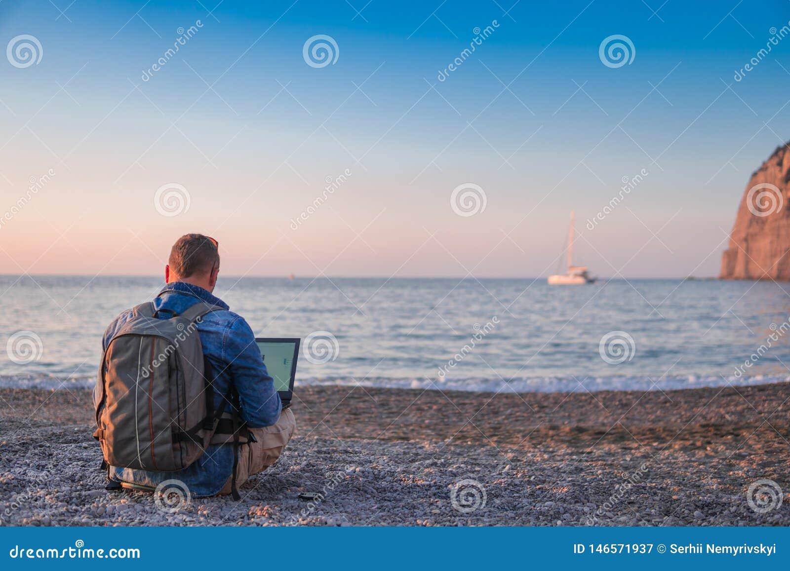Ung man med b?rbar datorarbete p? stranden Frihet, avl?gsna arbets-, freelancer-, teknologi-, internet-, lopp- och semesterbegrep