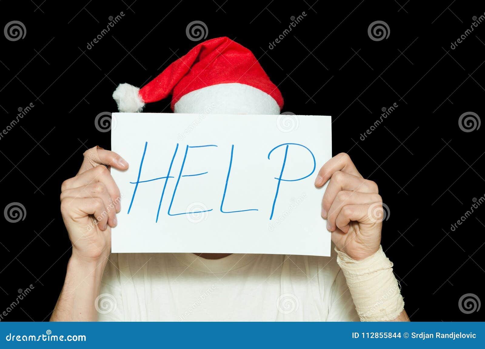 Ung man med den Santa Claus hatträkningen hans framsida med hjälptecknet efter det självmords- försöket som känner sig ensamt och