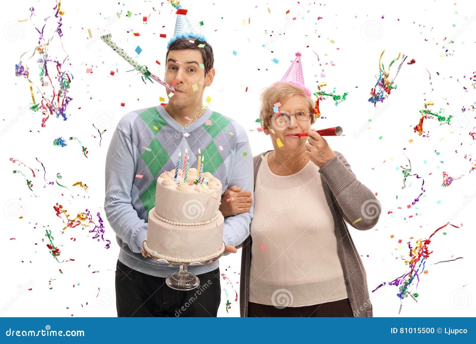 Ung man med födelsedagkakan och den mogna kvinnan som blåser partihornet