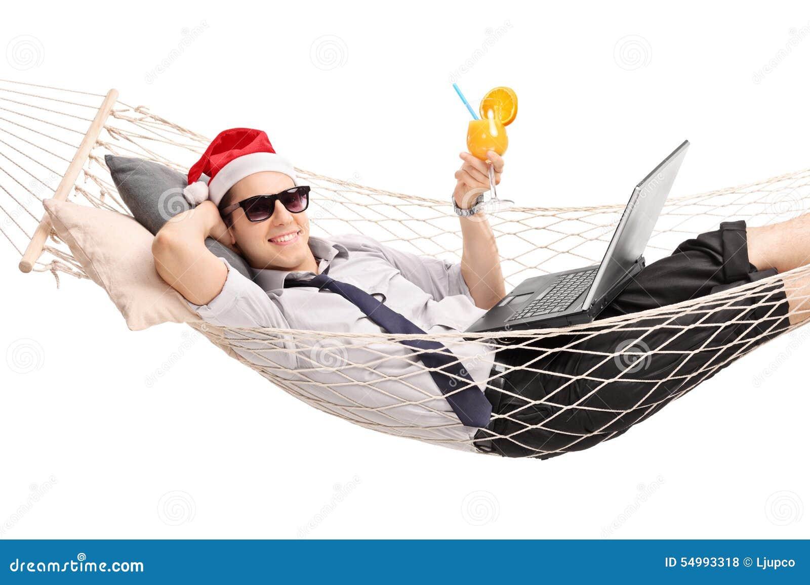 Ung man med jultomtenhatten som ligger i en hängmatta