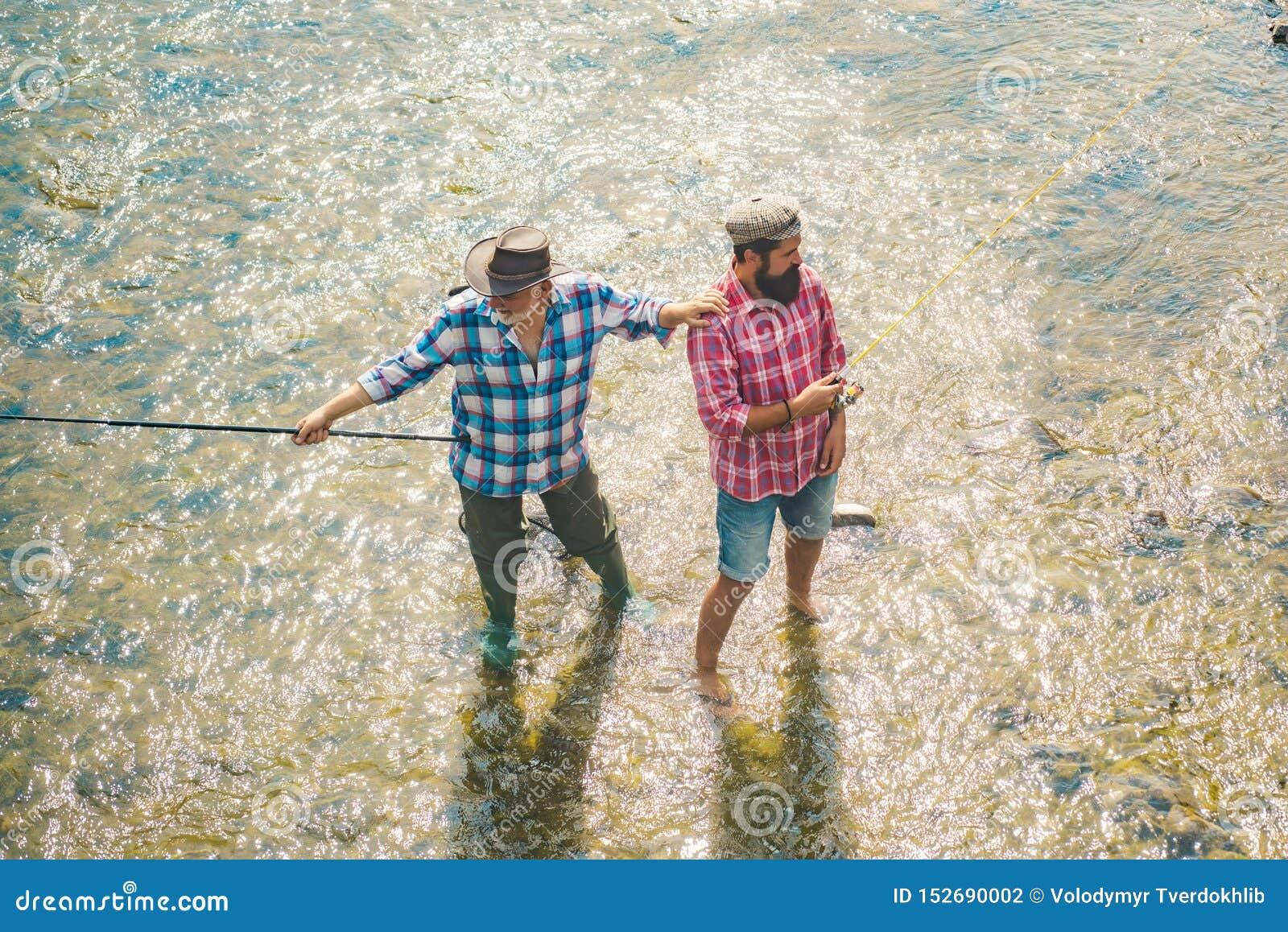 Ung man och gammalt moget manflugafiske Farfar och pojke som tillsammans fiskar Flyga stången och rullen med en brun forell från