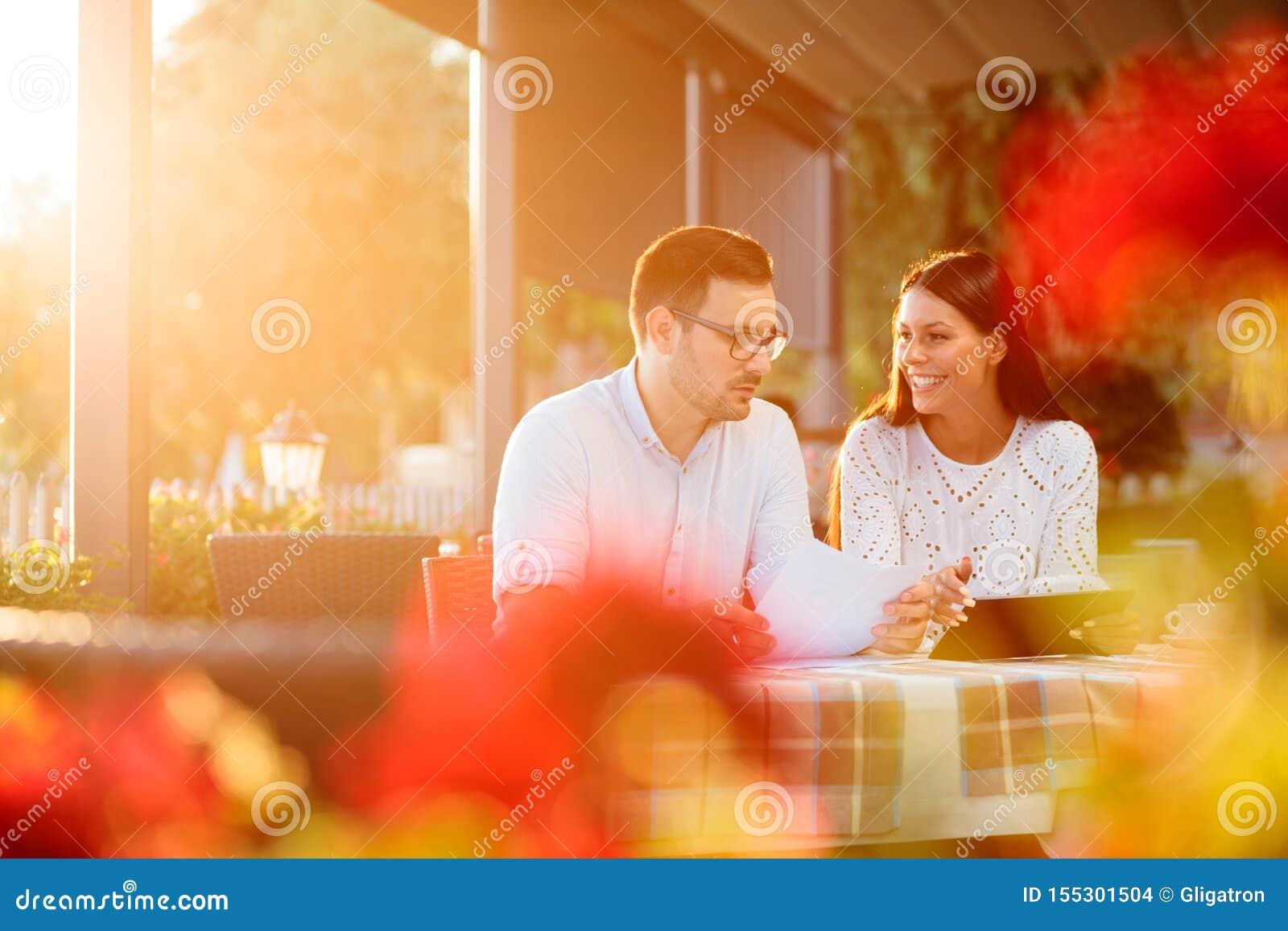 Ung man och kvinnligt affärsfolk som har ett tillfälligt arbetsmöte i ett flodstrandkafé