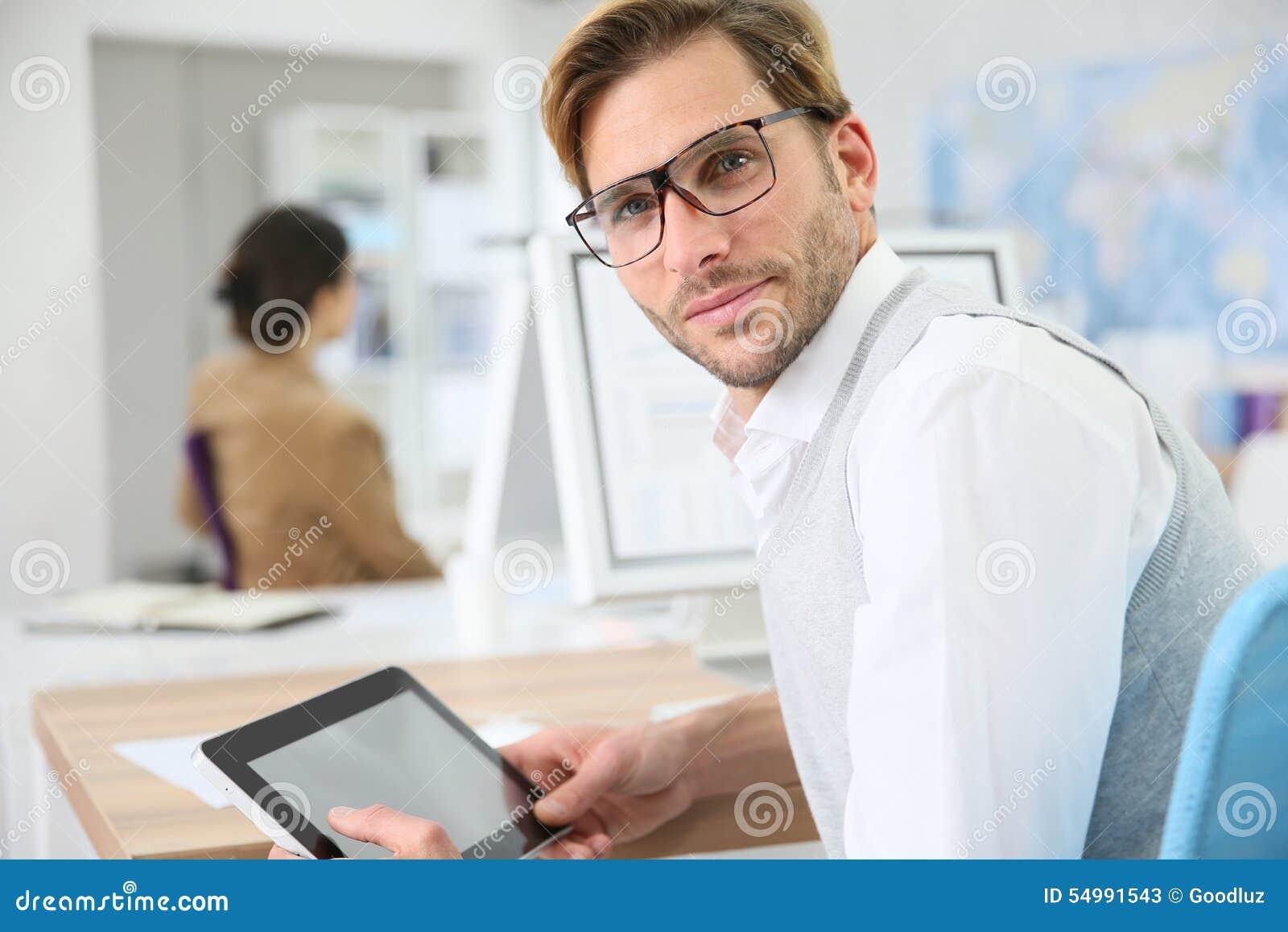 Ung man på kontoret genom att använda minnestavlan
