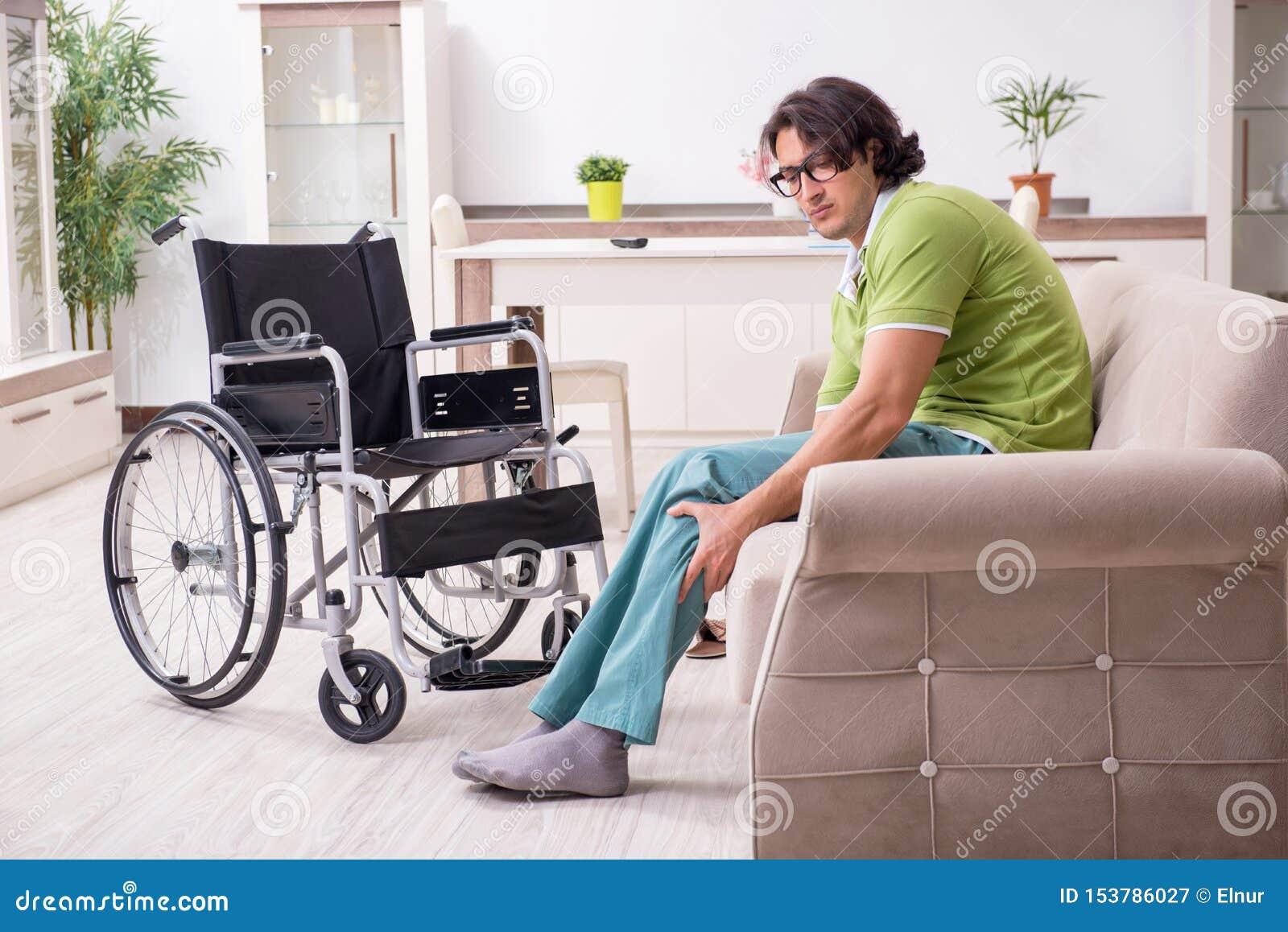 Ung man som är ogiltig i rullstolen som hemma lider