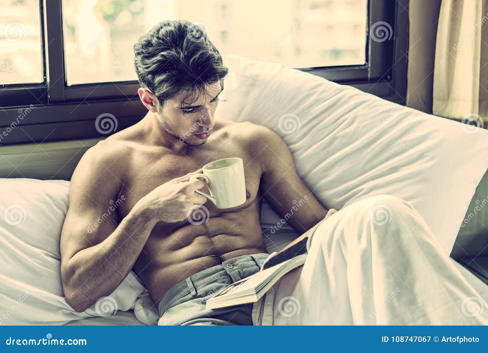 Ung man som är shirtless på hans säng med en kaffe- eller tekopp