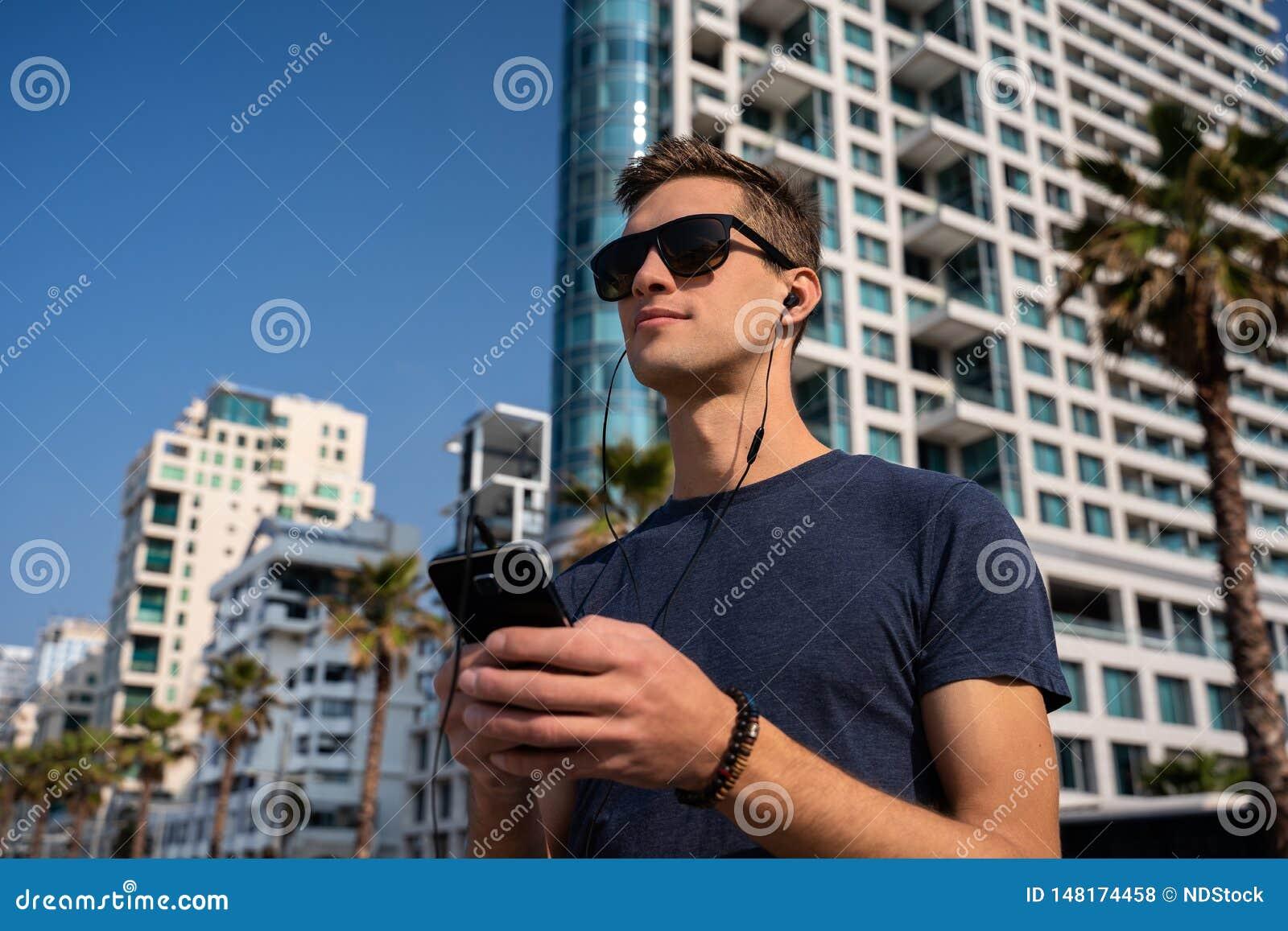 Ung man som använder telefonen med hörlurar med mikrofon Stadshorisont i bakgrund