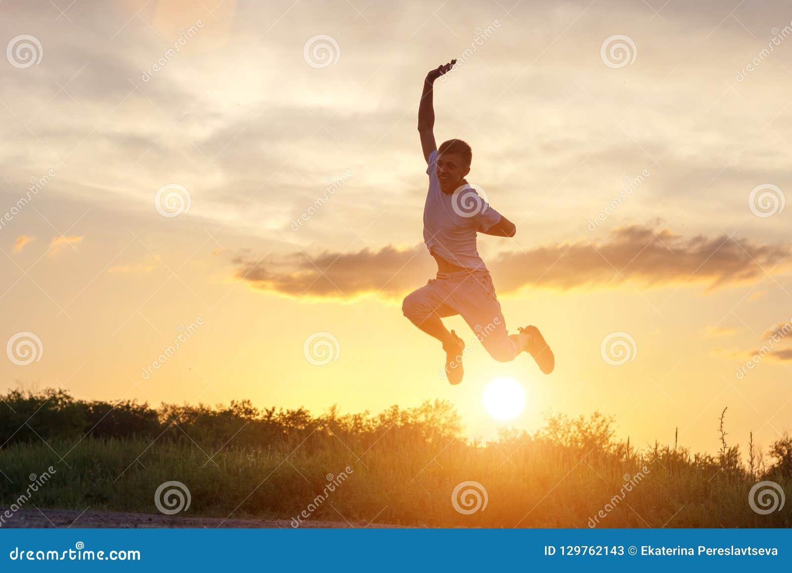 Ung man som hoppar upp mot solnedgånghimlen