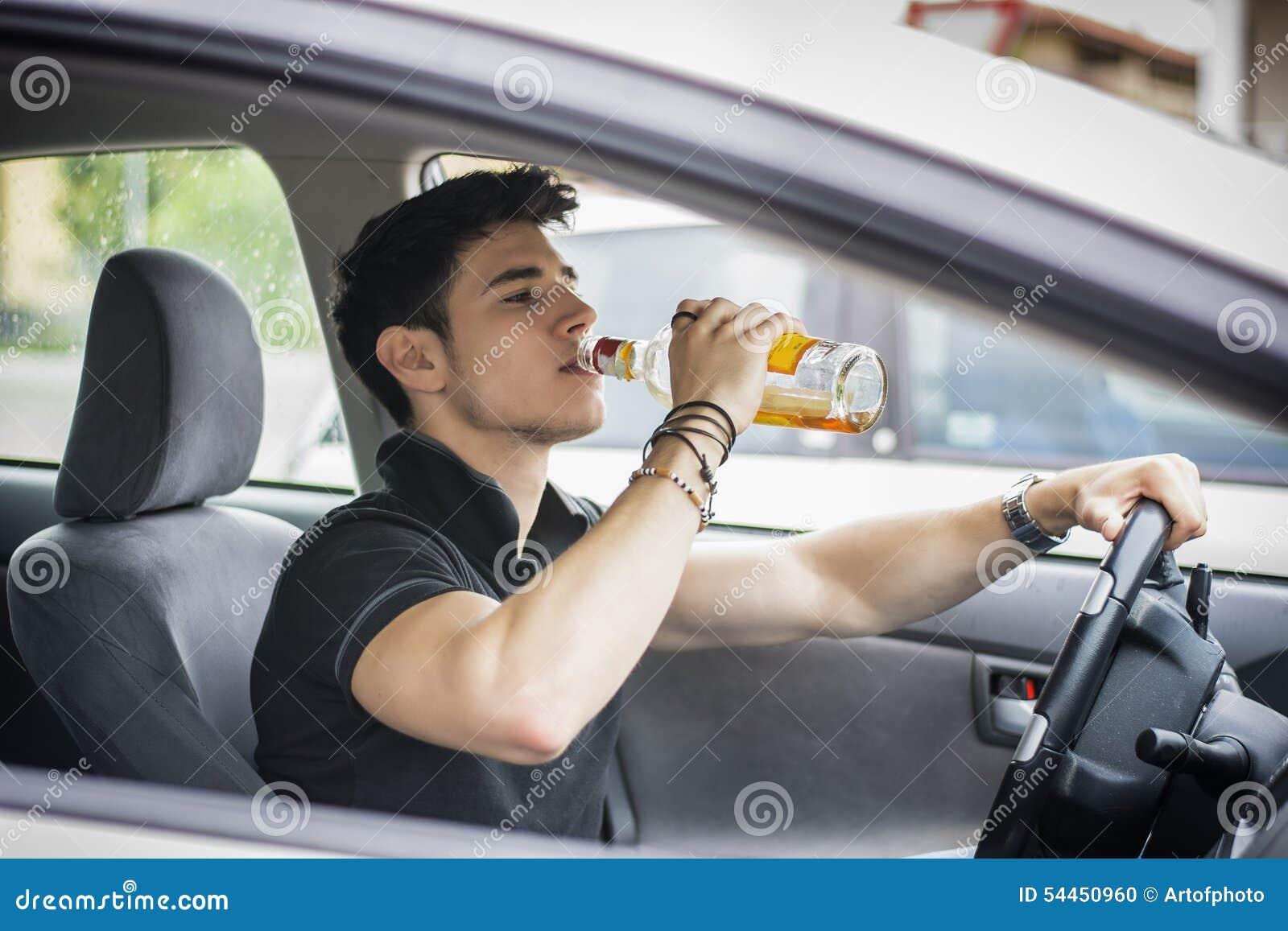 Ung man som kör hans bil, medan dricka alkohol