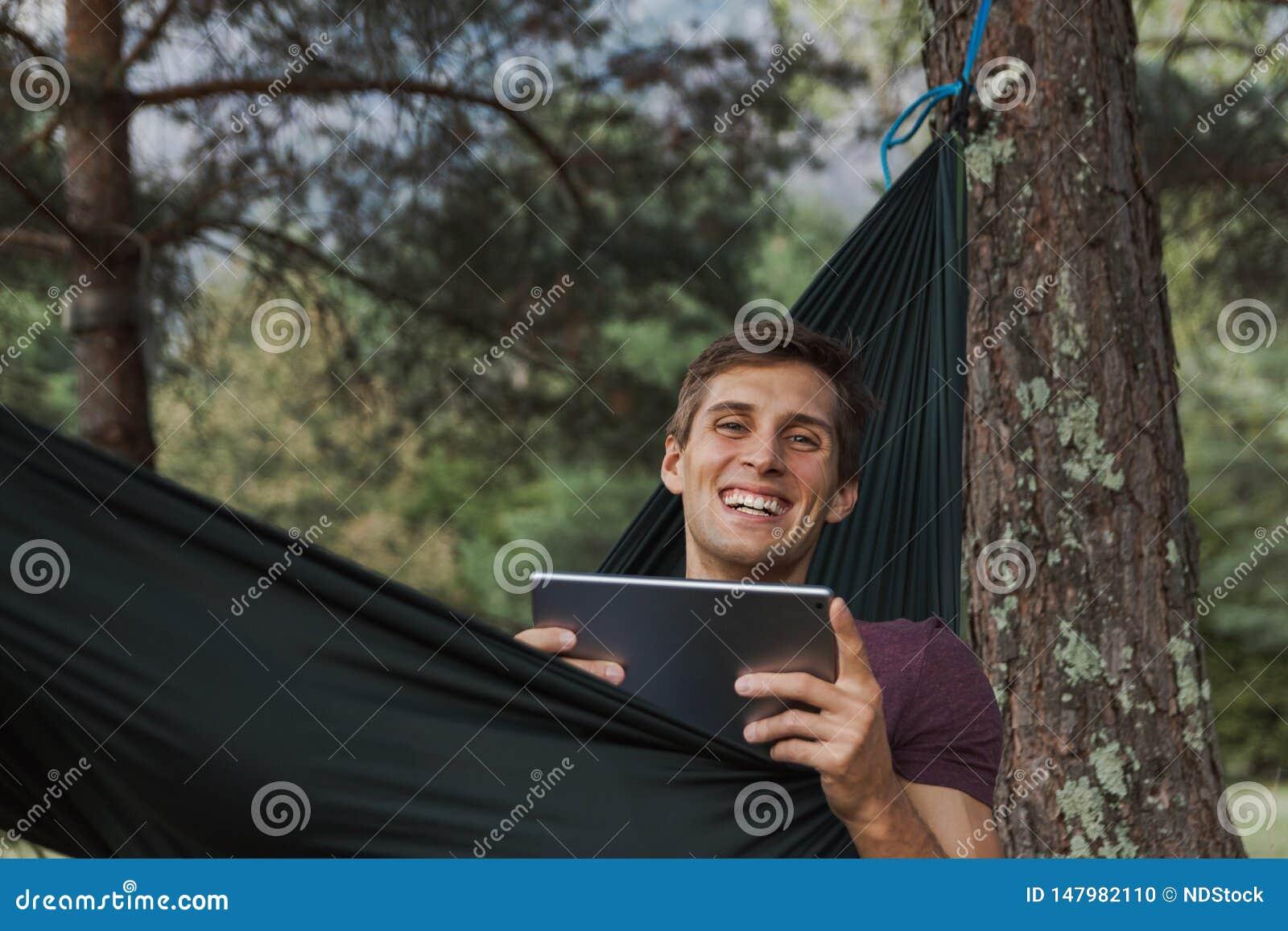 Ung man som ler till kameran och använder en minnestavla på en hängmatta