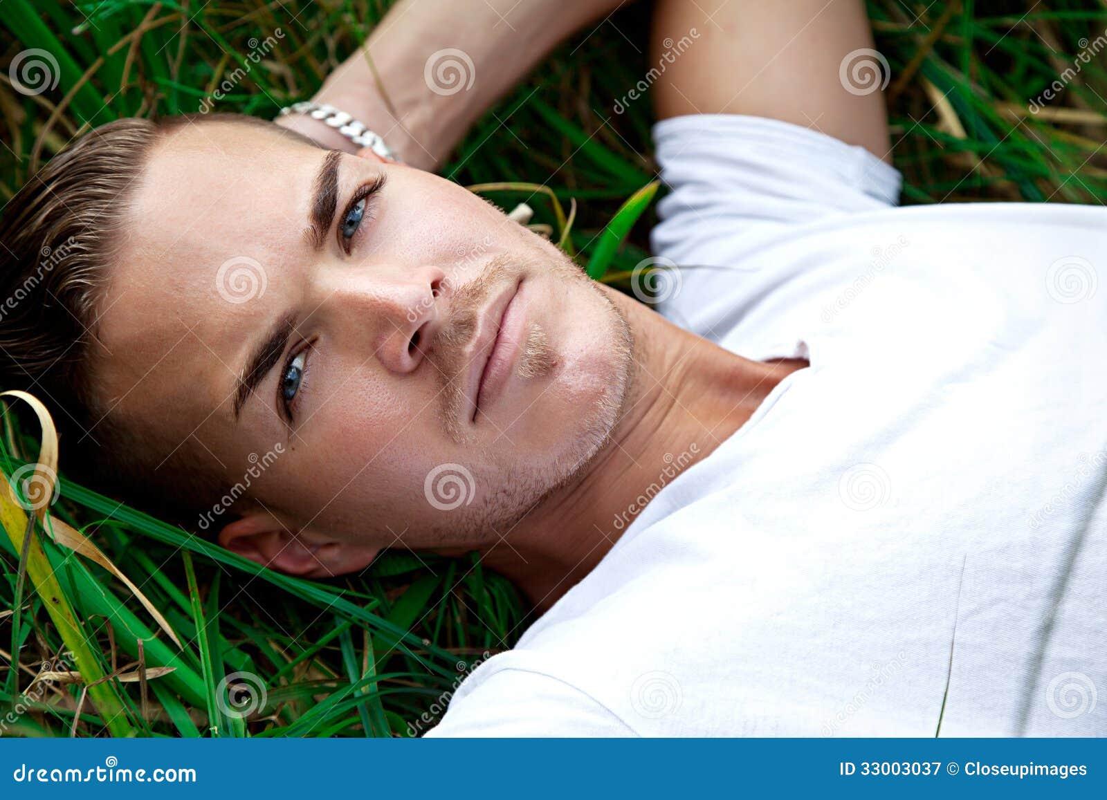 Ung man som ligger på gröna gras