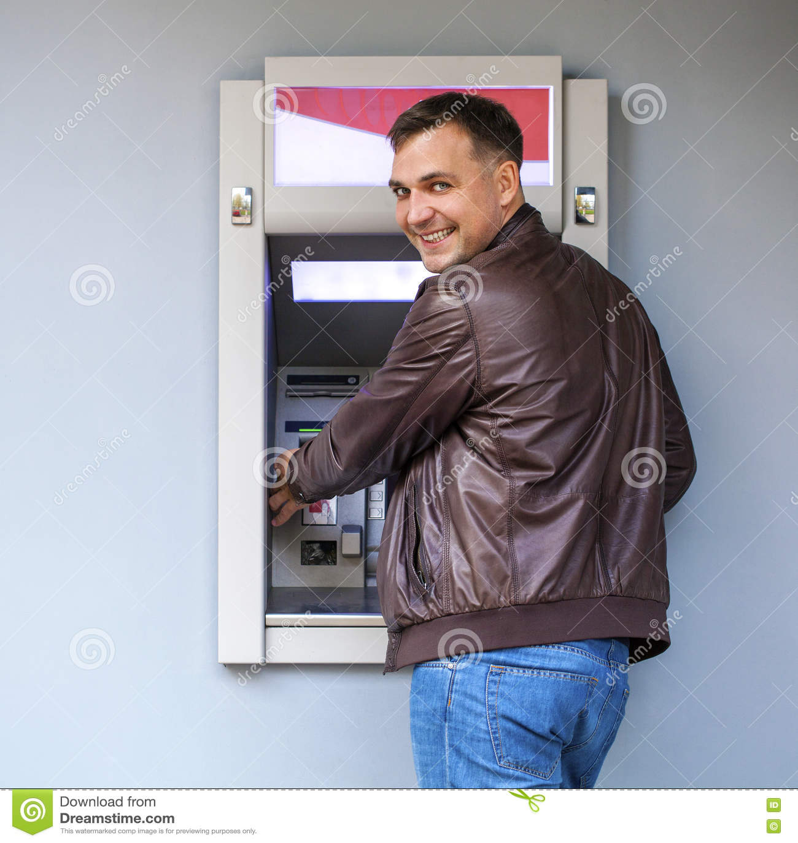 Ung man som sätter in en kreditkort till ATM