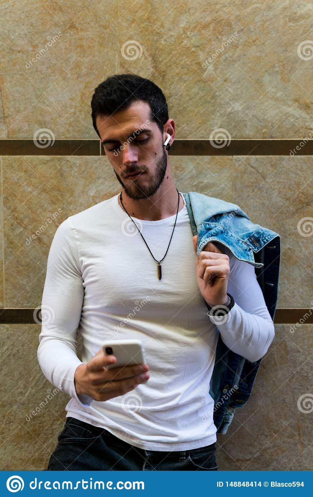 Ung man som ser smartphonen i gatan modern bakgrund