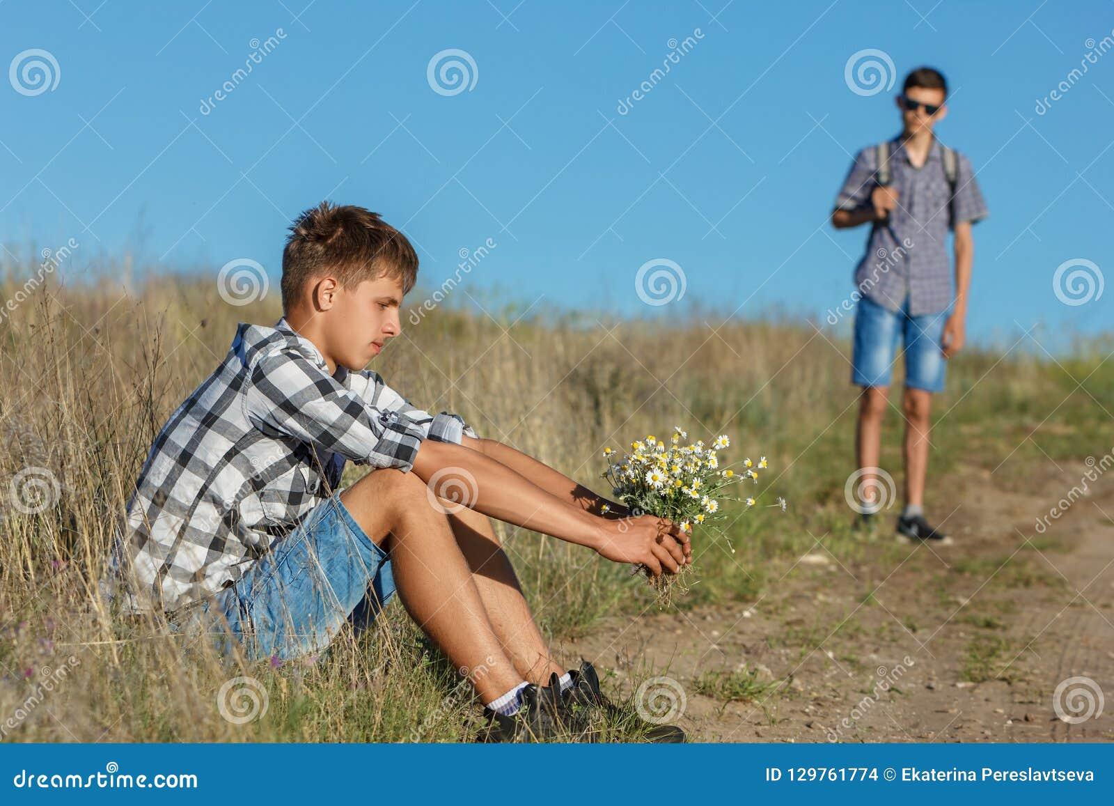 Ung man som sitter vid vägen med blommor som väntar på andra, begreppet av förhållandet