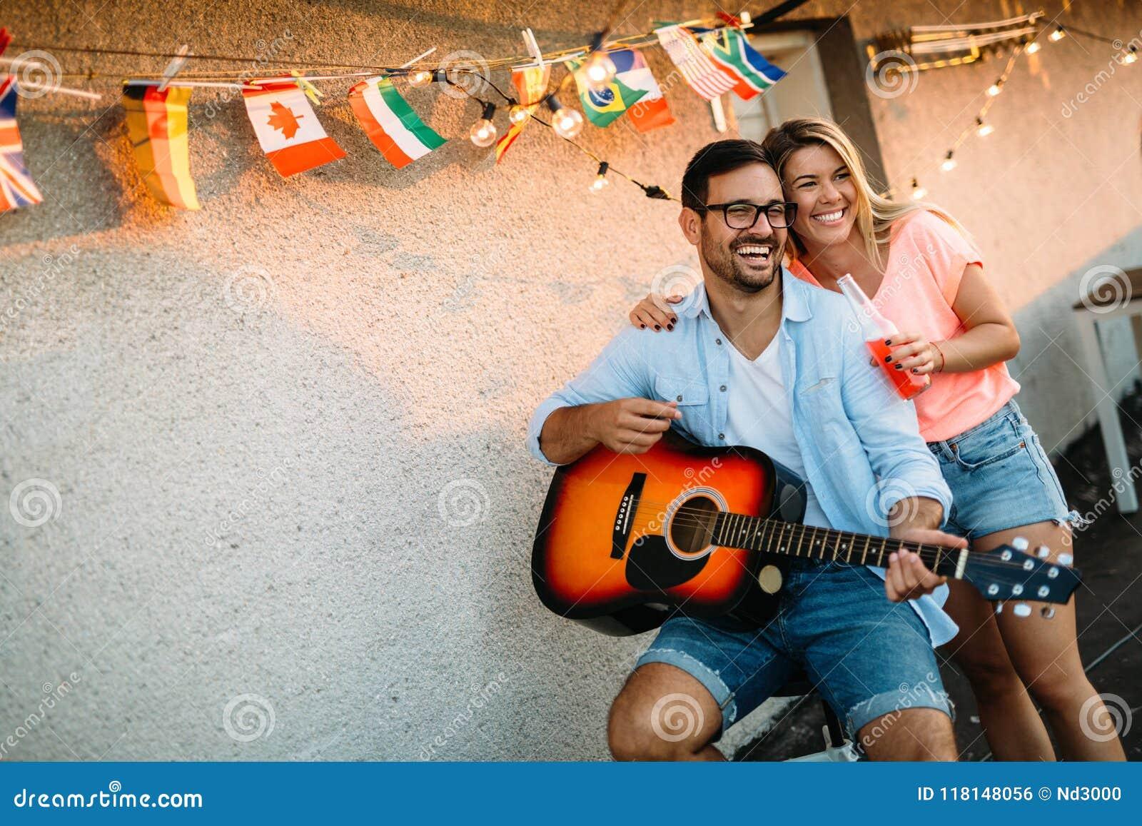 Ung man som spelar gitarren för vänner och hans flickvän