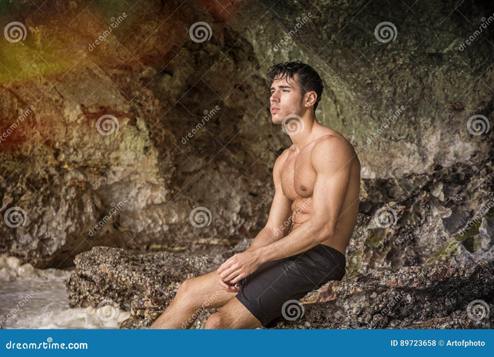 Ung man som står shirtless, kullar i bakgrund