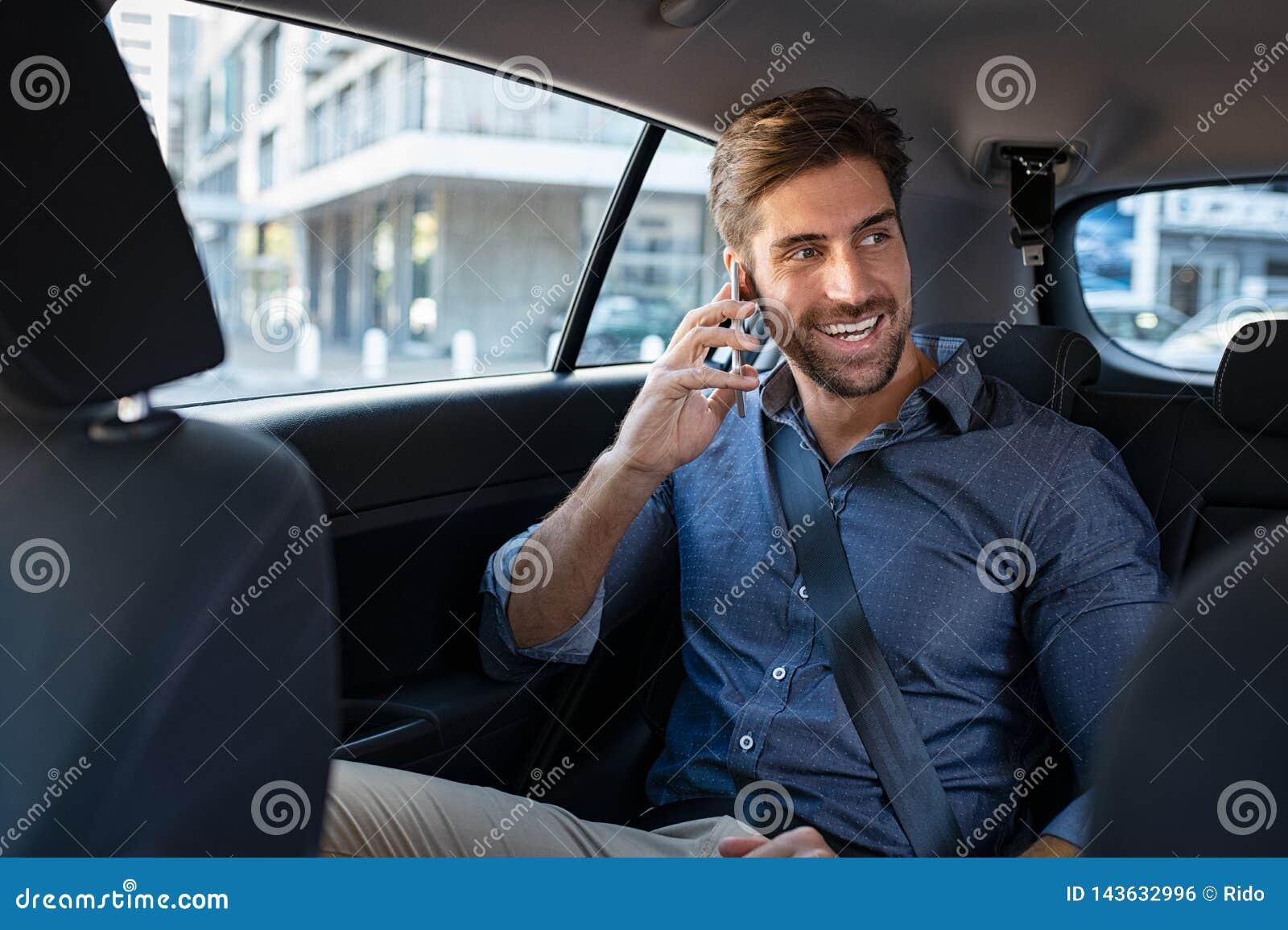 Ung man som talar över telefonen i taxi