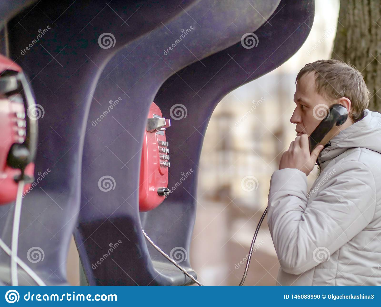 Ung man som talar på en röd gatapayphone