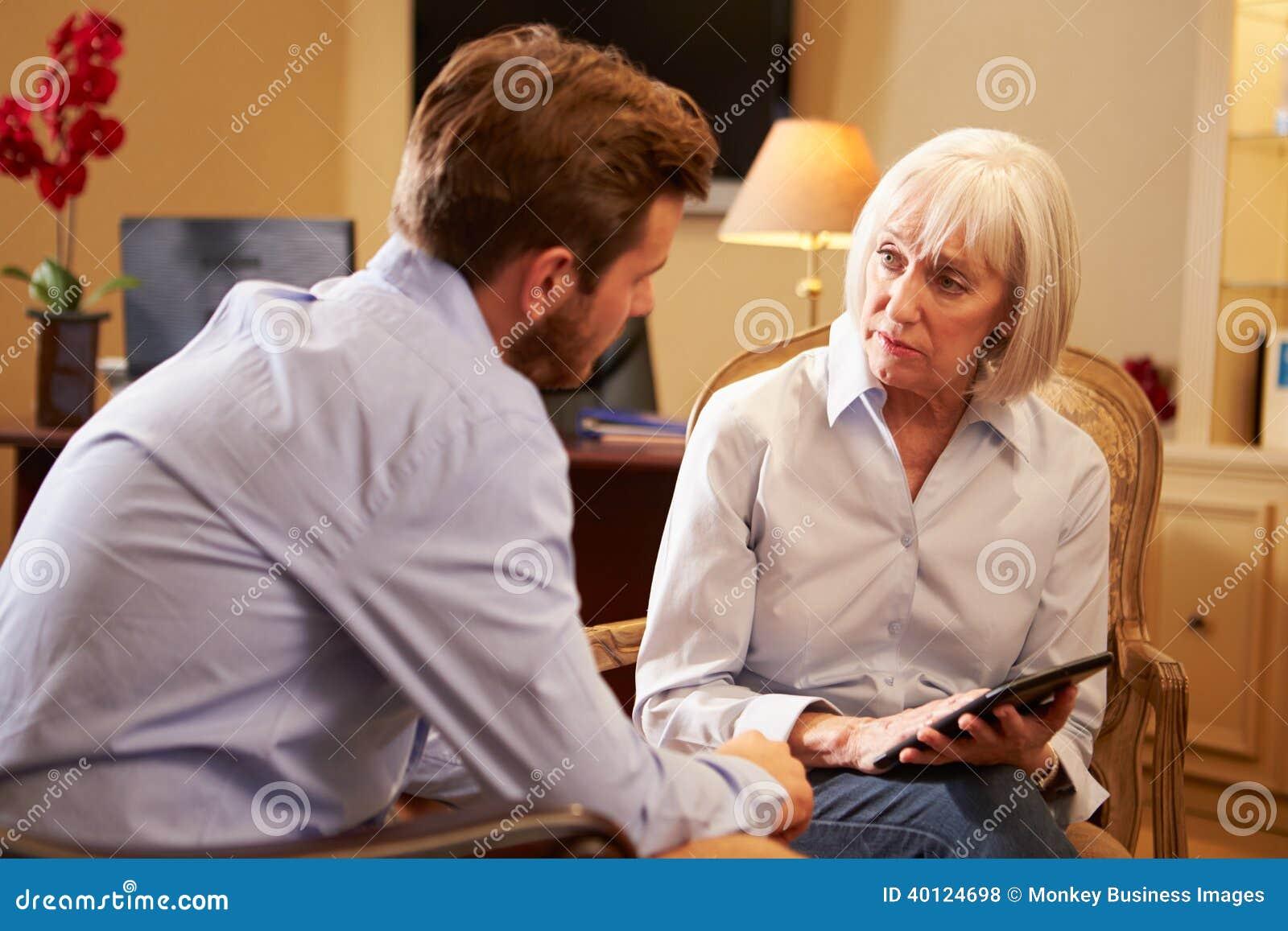 Ung man som talar till rådgivaren som använder den Digital minnestavlan