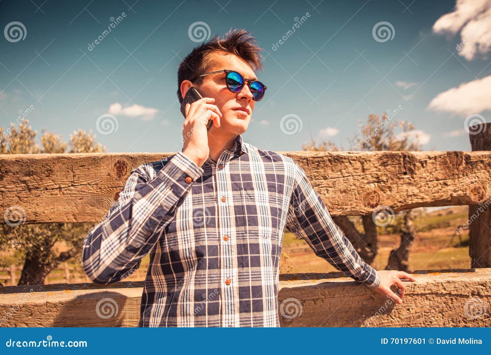 Ung man som talar vid telefonen i bygden