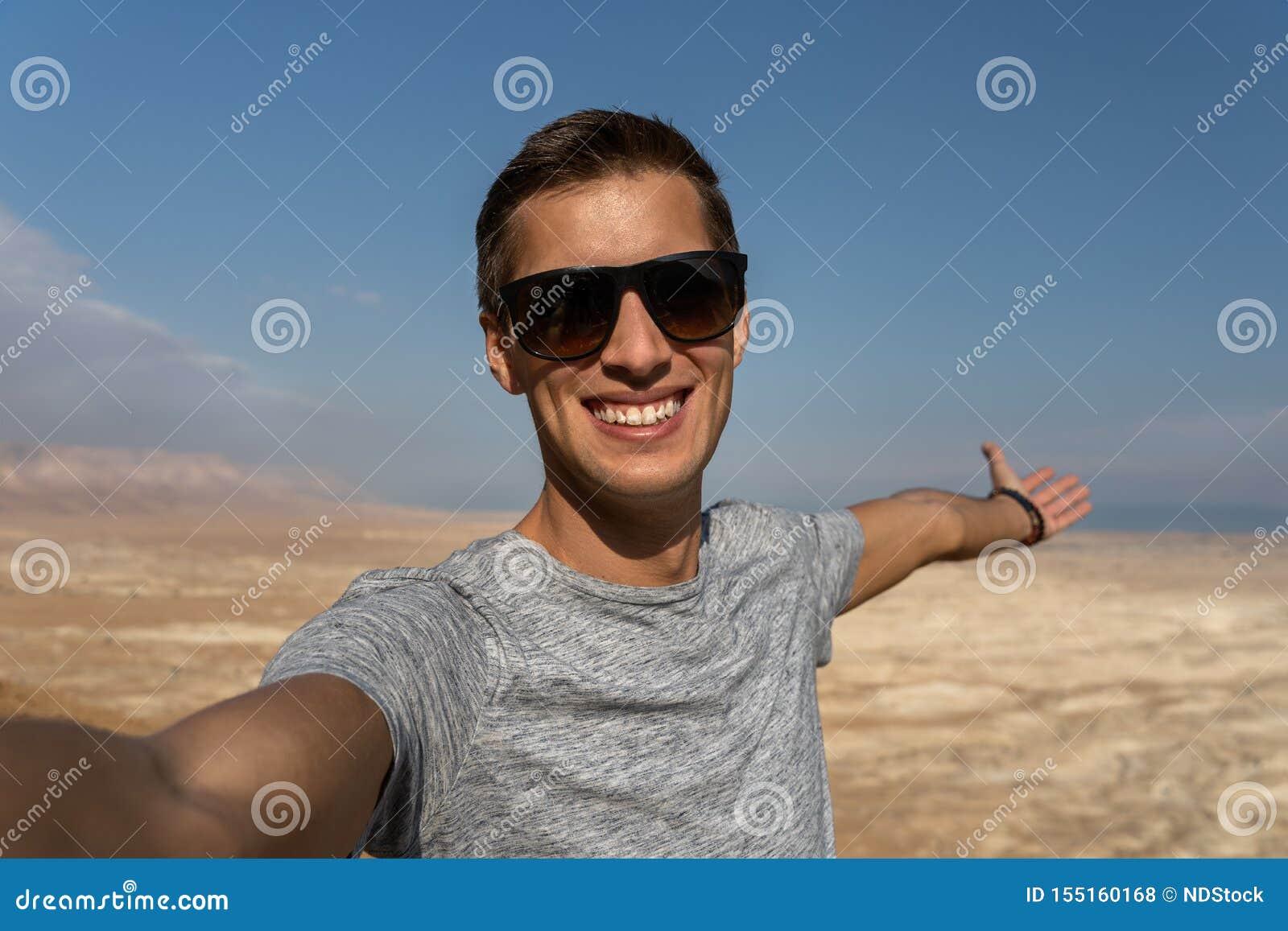 Ung man som tar en selfie i öknen av Israel