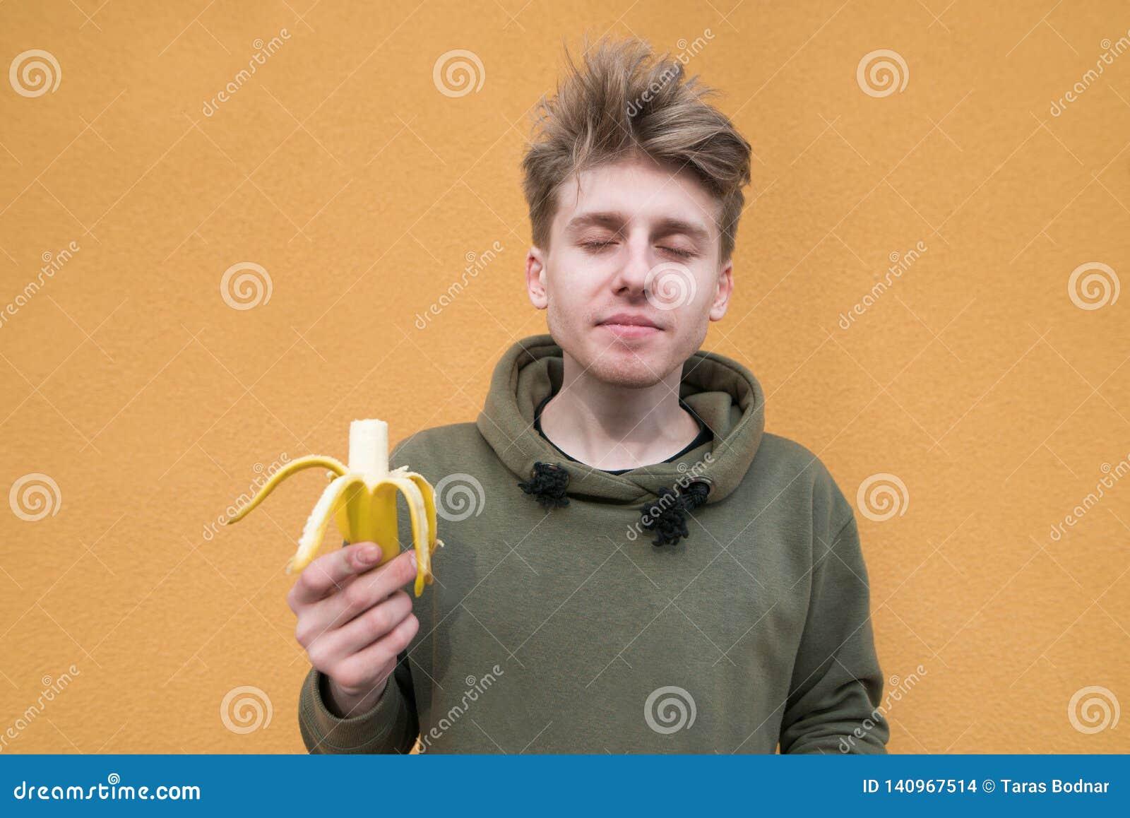 Ung man som tycker om bananmellanmålet En läcker banan för lunch på bakgrunden av en orange vägg