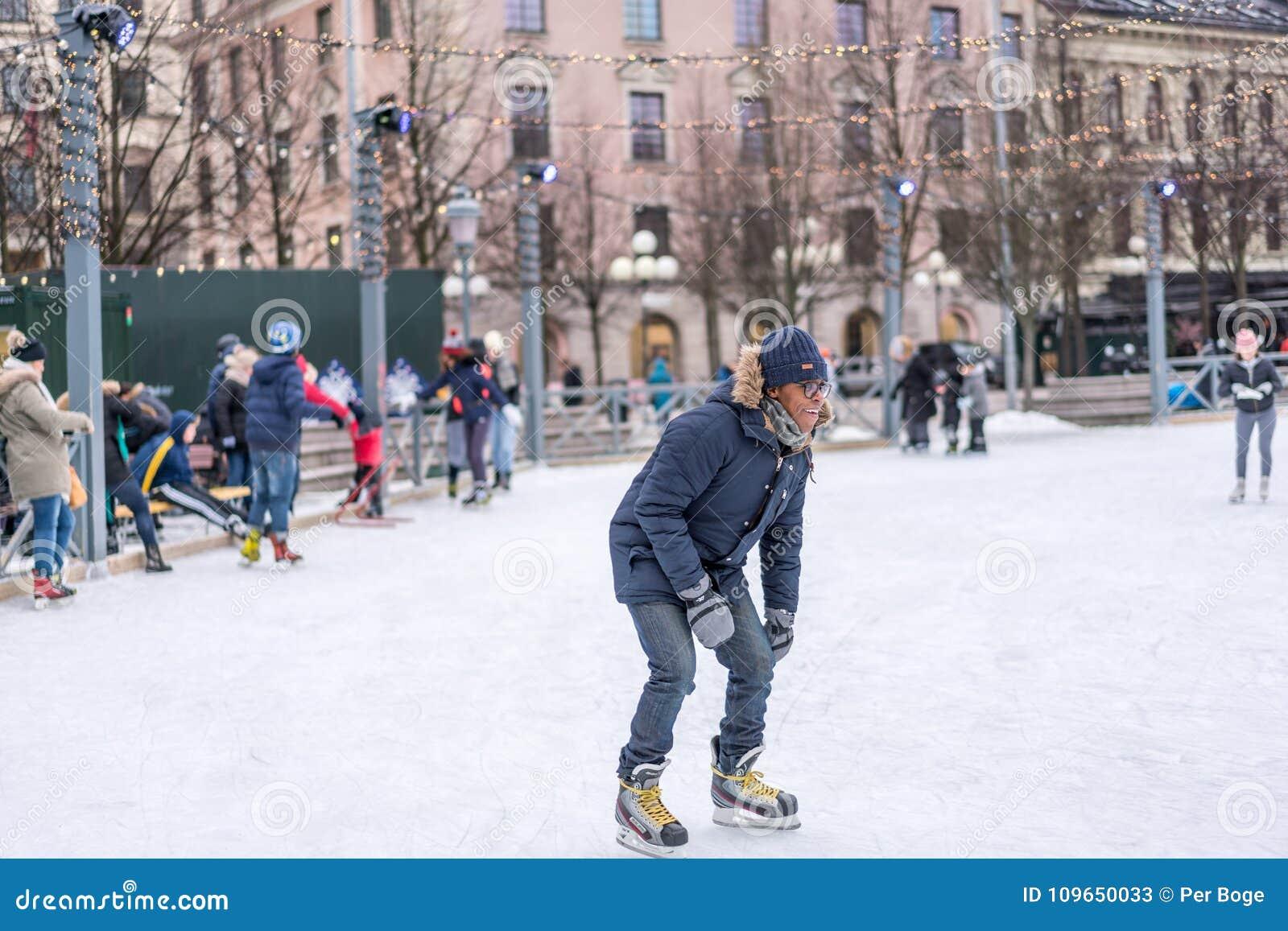 Ung man som utomhus åker skridskor på en offentlig skridskoåkningisbana i staden