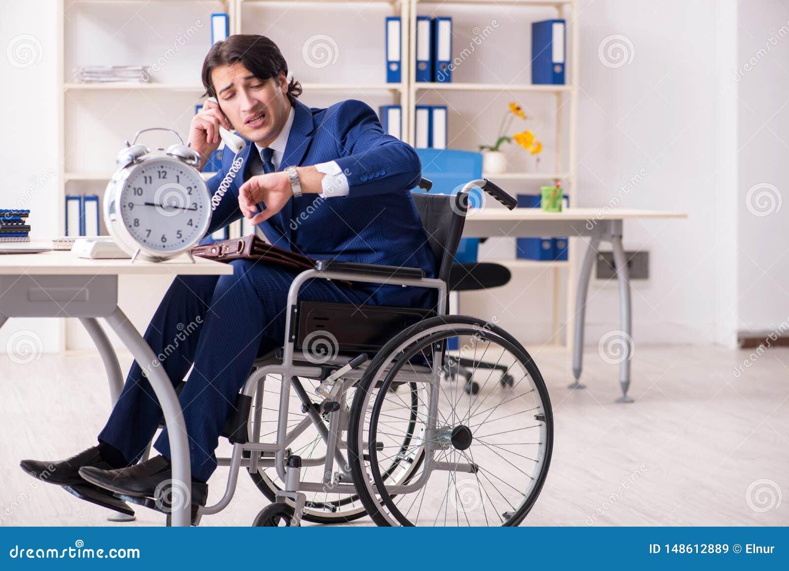 Ung manlig anst?lld i rullstolarbete i kontoret
