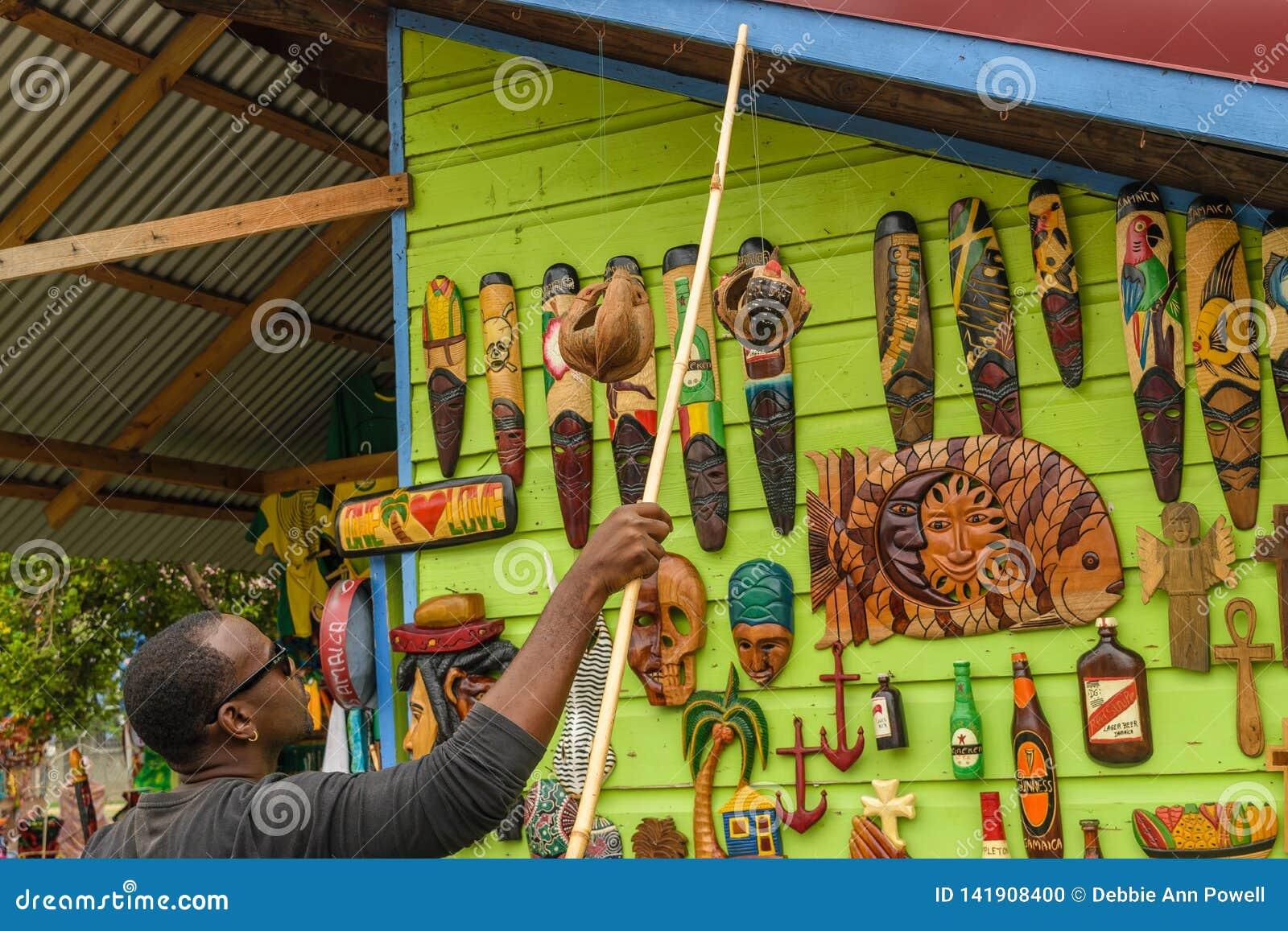Ung manlig försäljare som säljer väggkonstträskulpturer på hantverkmarknaden