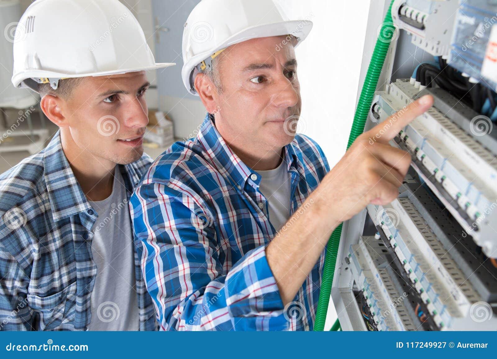 Ung manlig tekniker som lär att undersöka fusebox med multimetersonden