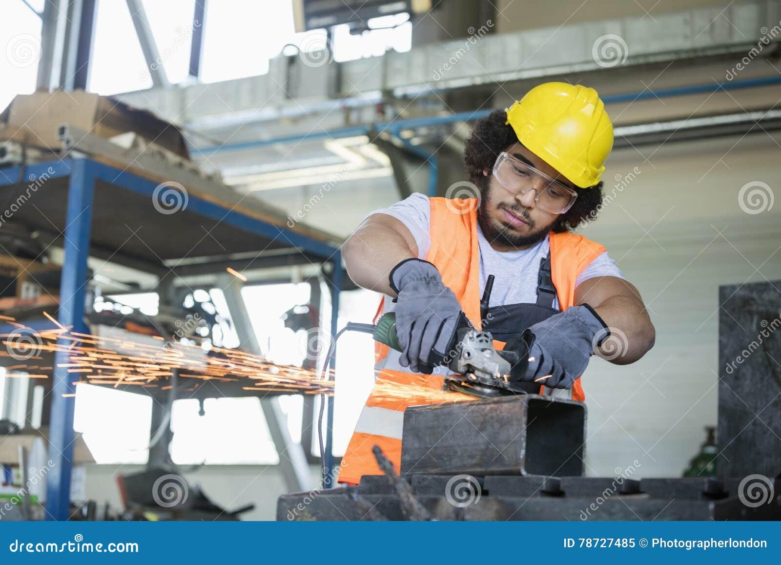 Ung manuell arbetare i skyddande workwearklippmetall i bransch