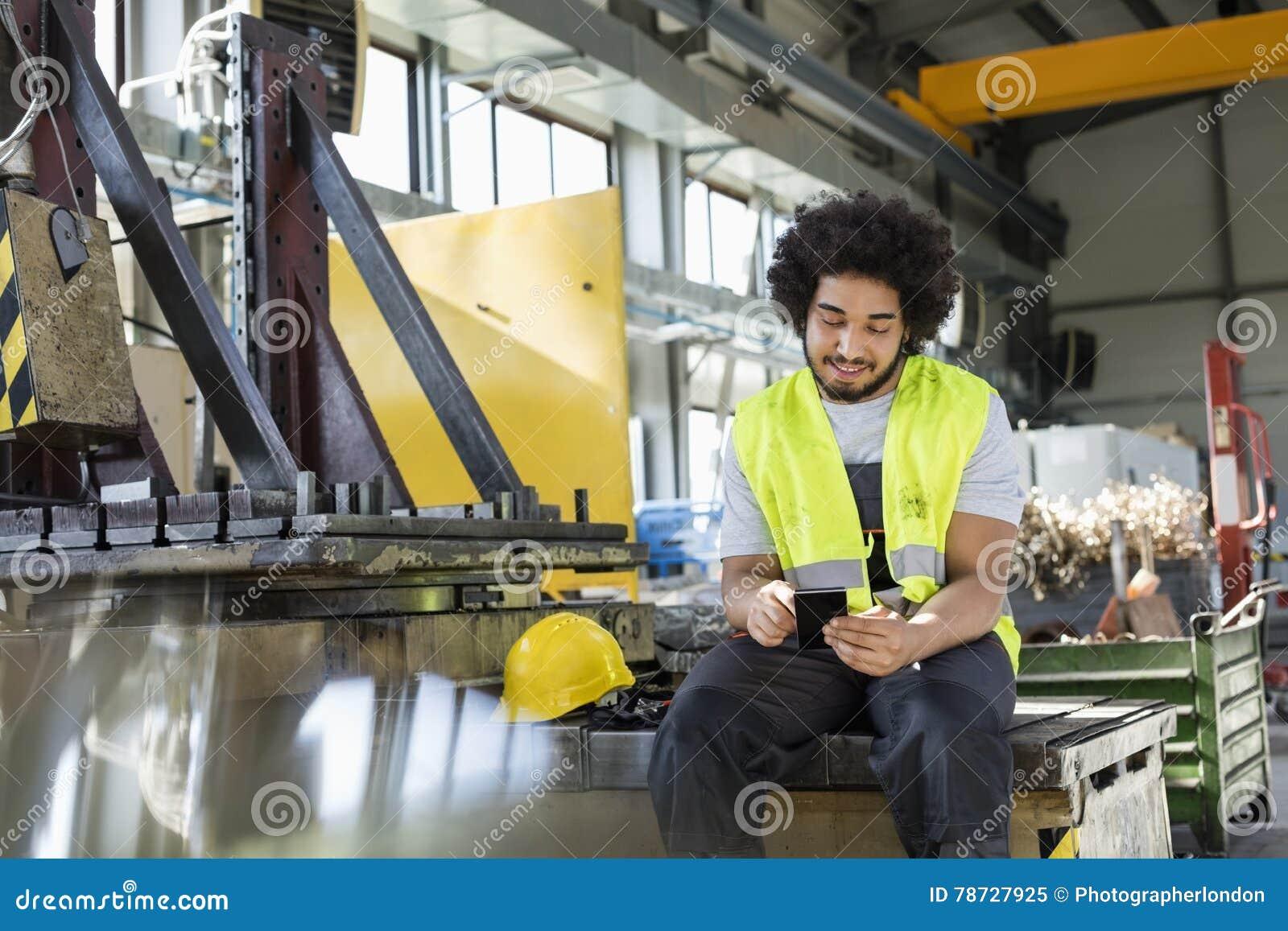 Ung manuell arbetare som använder mobiltelefonen i metallbransch