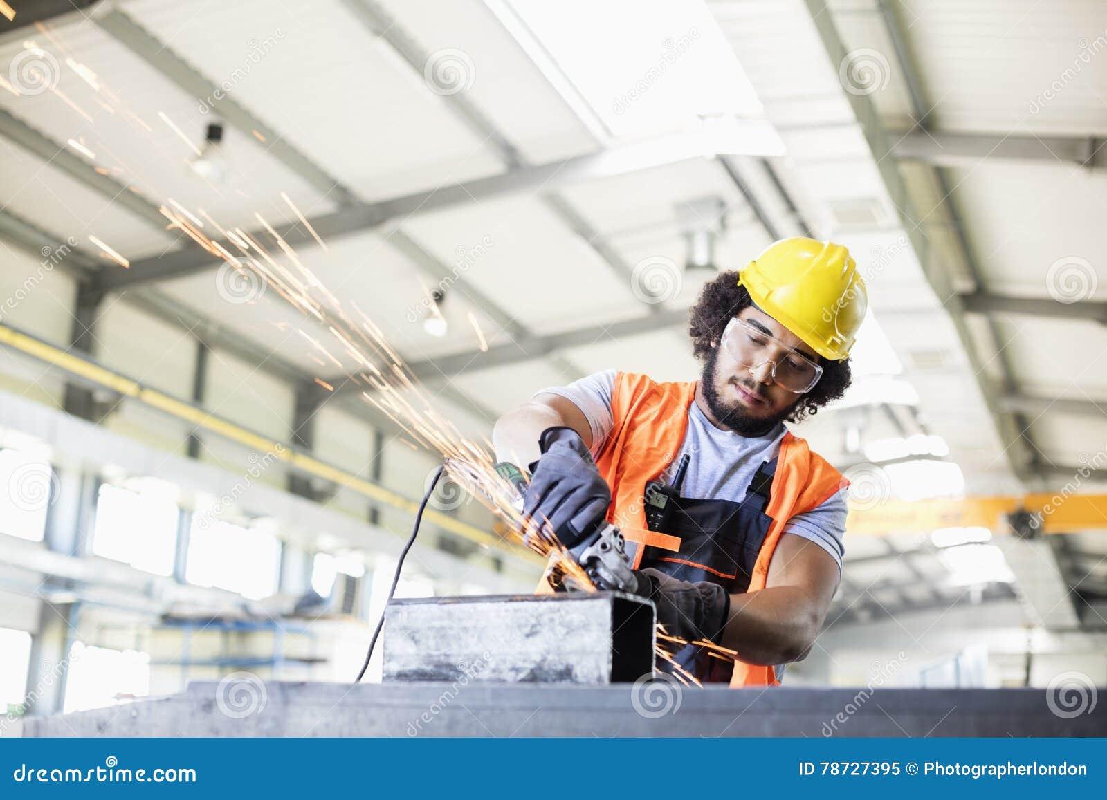 Ung manuell arbetare som använder molar på metall i fabrik