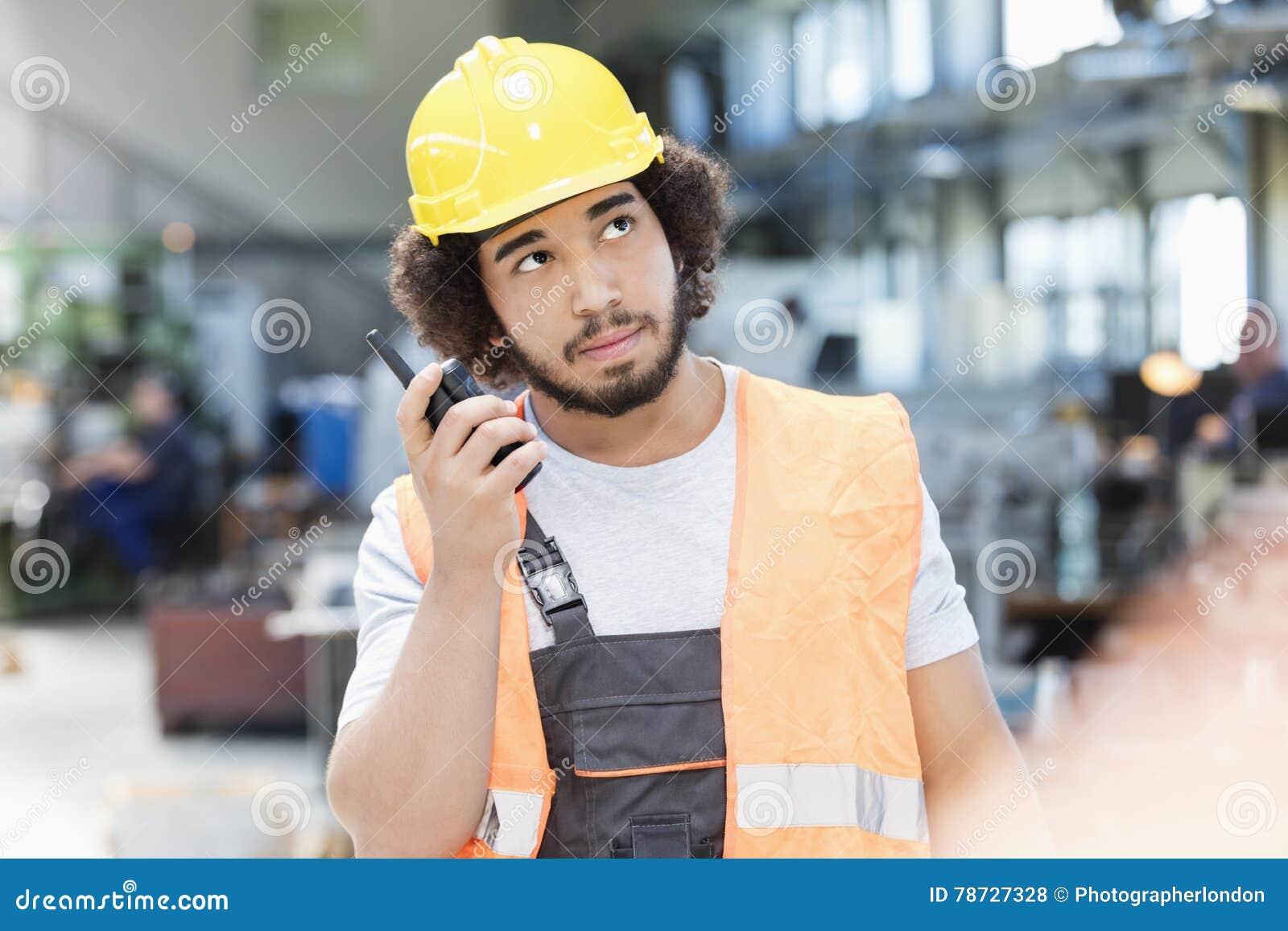 Ung manuell arbetare som lyssnar till walkie-talkie, medan se upp i metallbransch