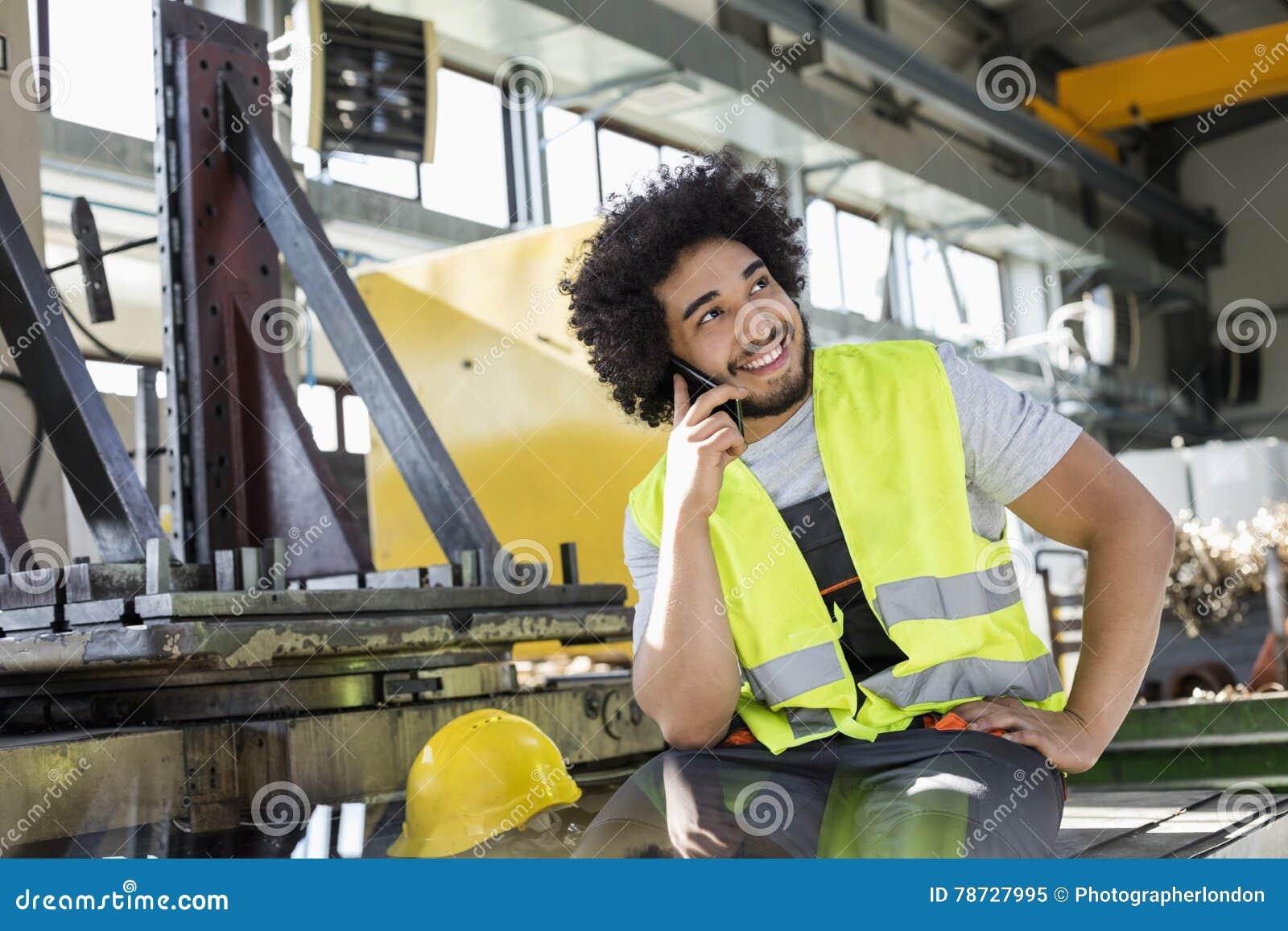 Ung manuell arbetare som talar på mobiltelefonen i metallbransch