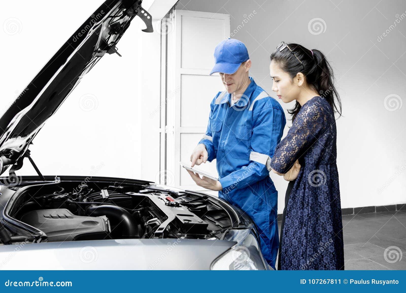 Ung mekaniker som talar med hans klient